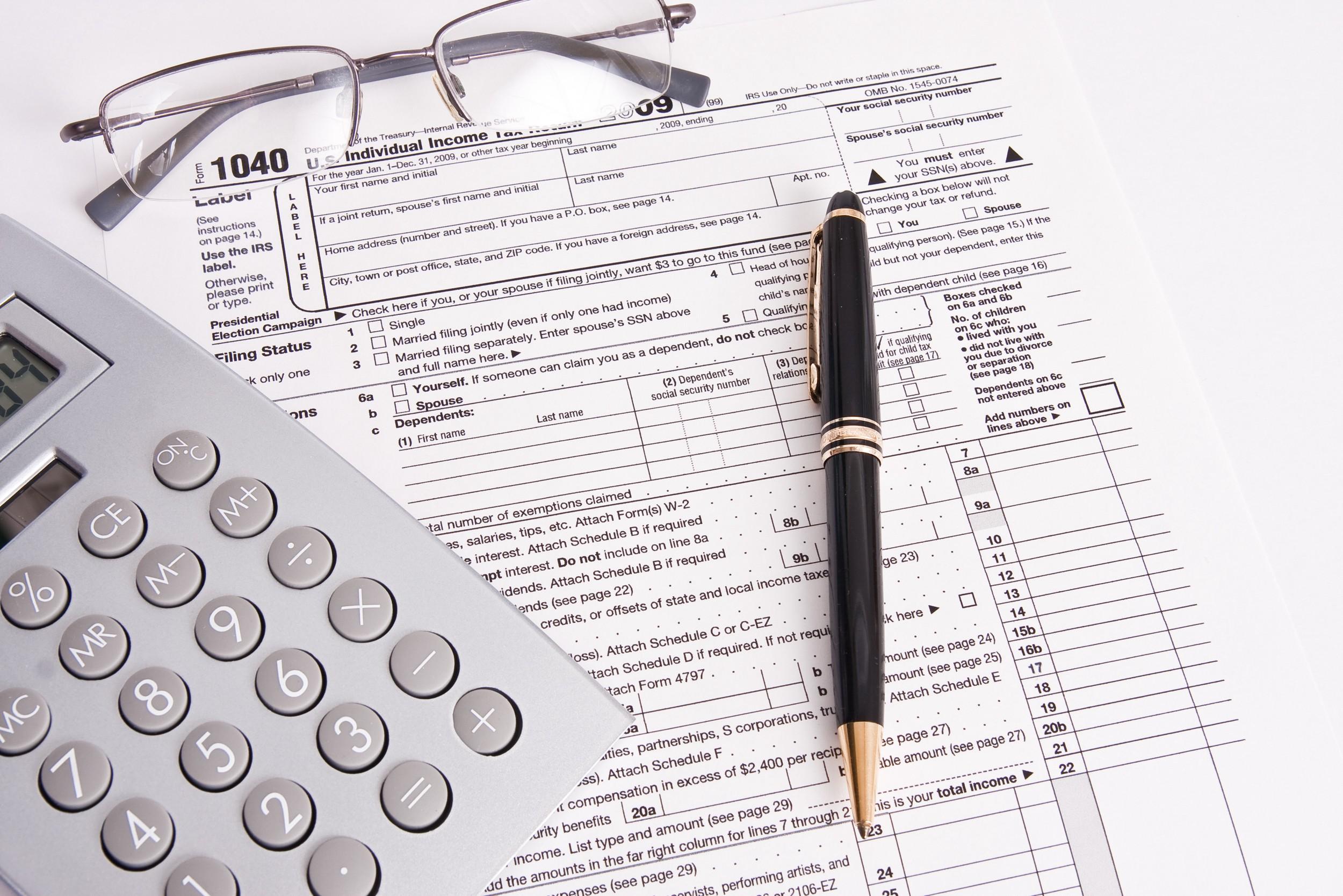 Income tax form with glasses, calculator and pen