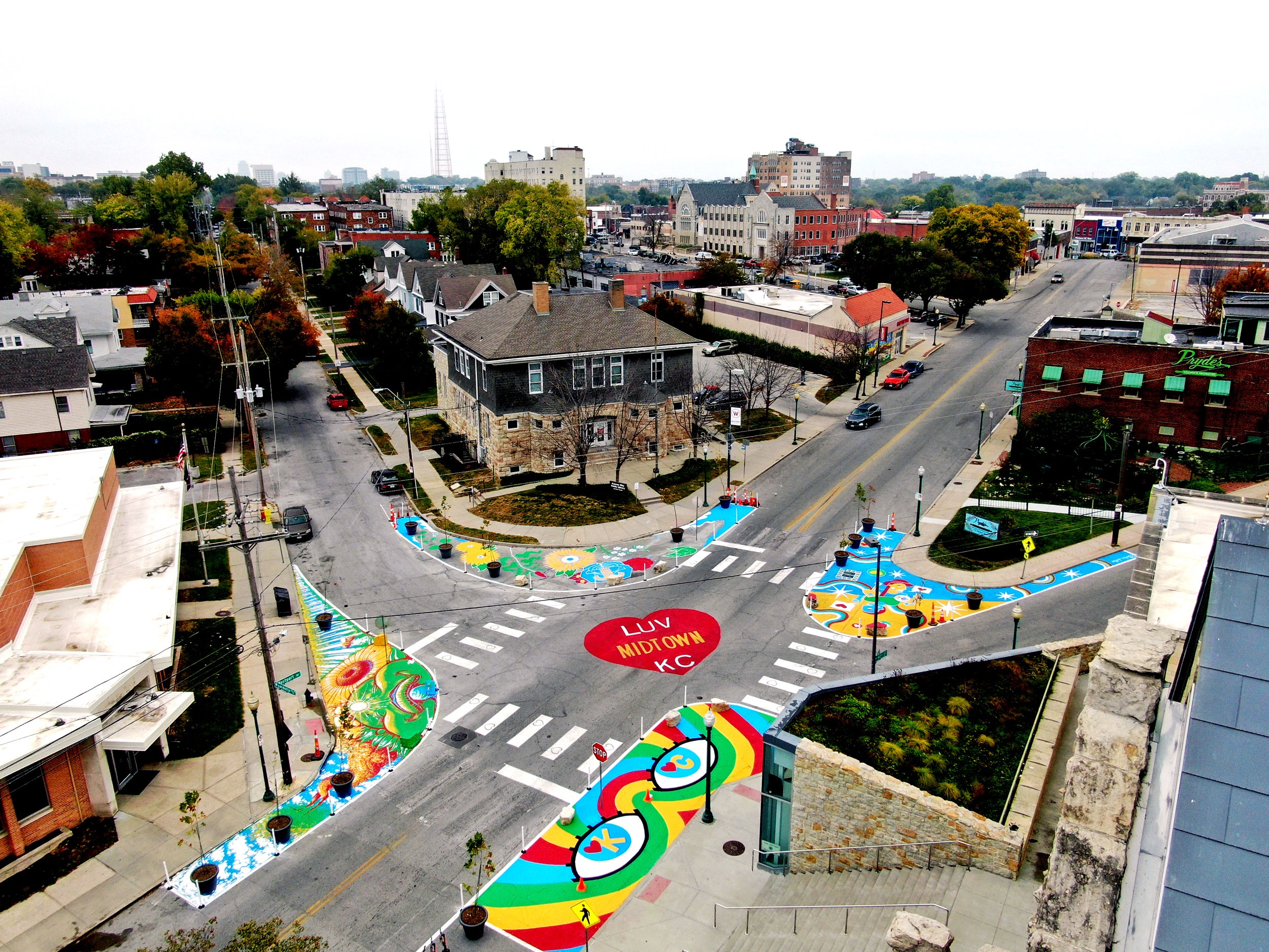 """An intersection is painted in bright colors. Paint narrows crossing distances and widens sidewalks, and a large red heart in the center reads """"LUV MIDTOWN K.C."""""""