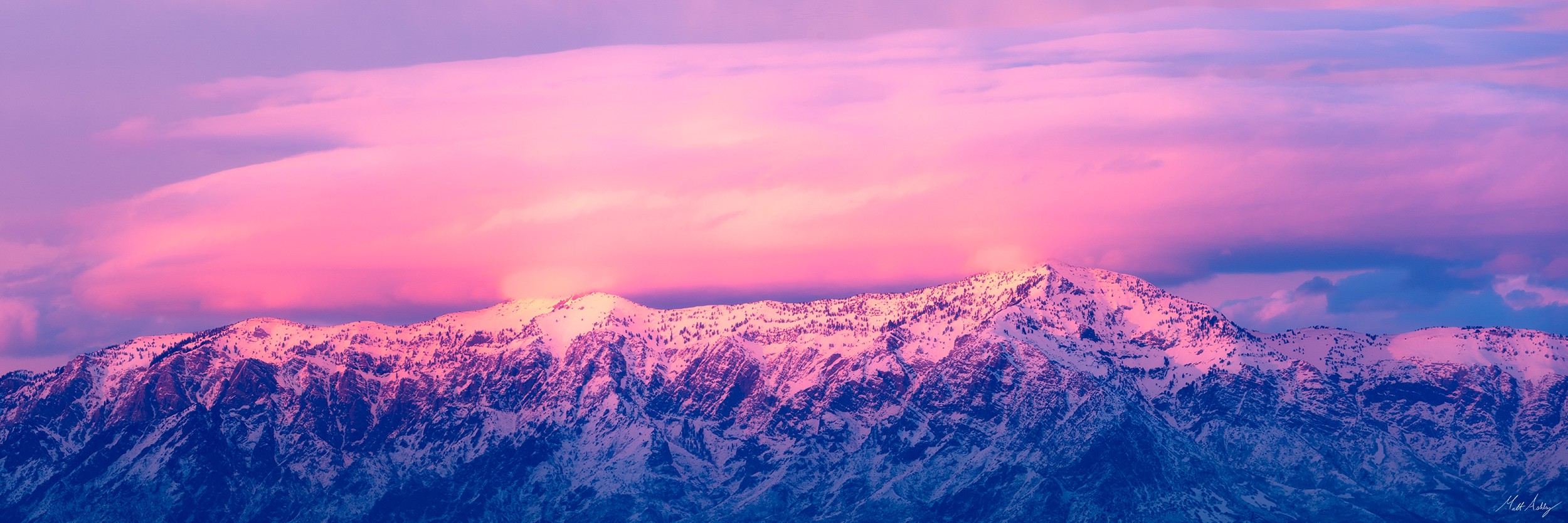 Mountain range at sunset under a brilliant pink sky.