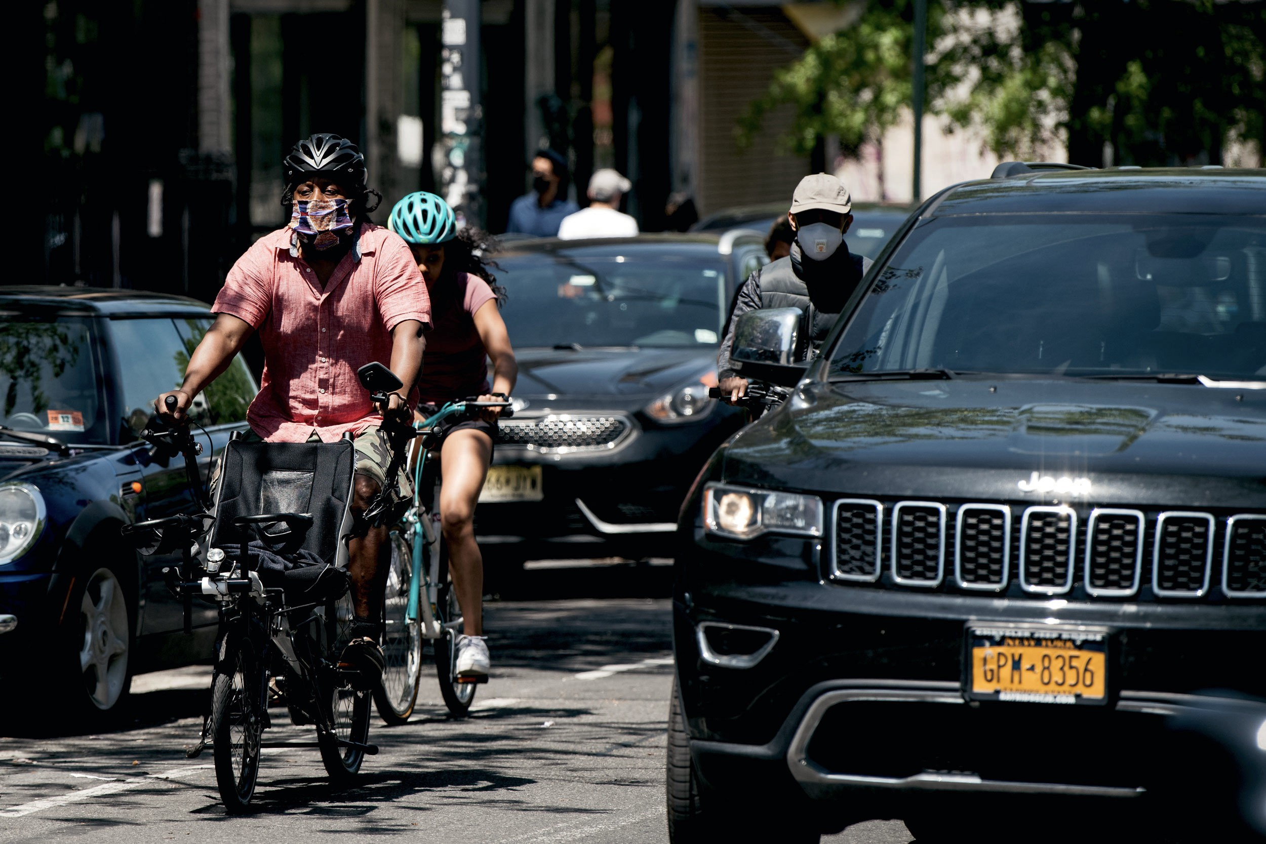 People on bicycles share a narrow street with imposing black SUVs.