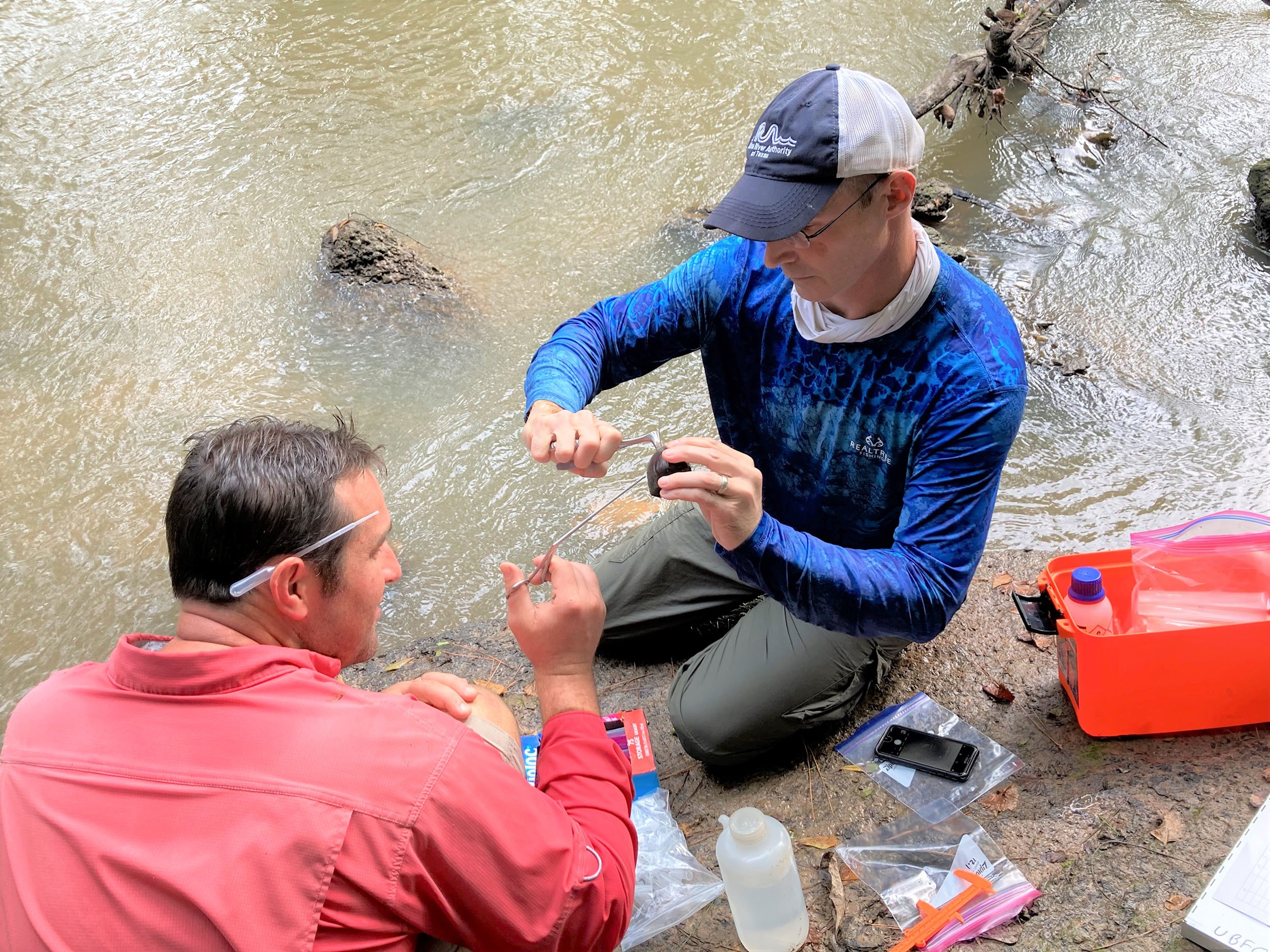 2 men kneel on muddy riverbank surrounded by bottles, cand, etc.; one holds muttel