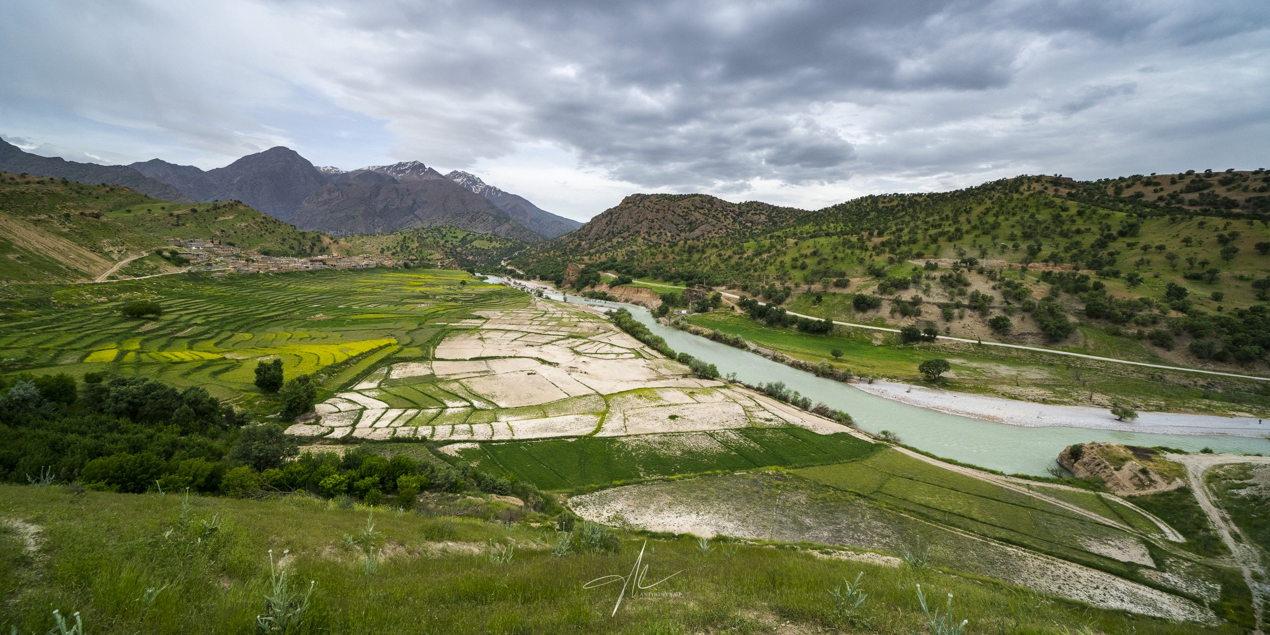 A vast valley of local settlement, terraced rice fields, roaming river, and looming sky.