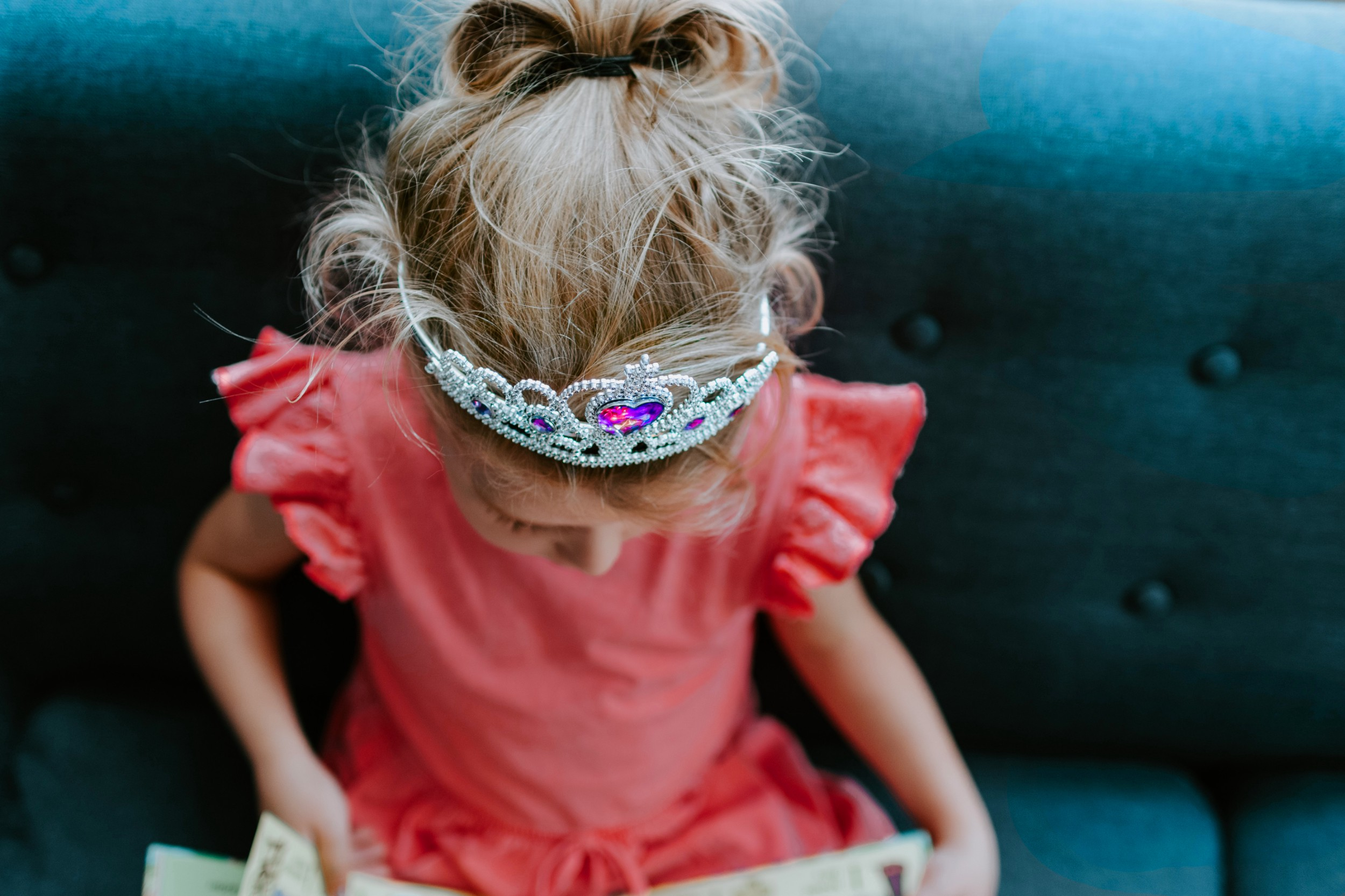 Little girl on a sofa wearing plastic crown while reading.
