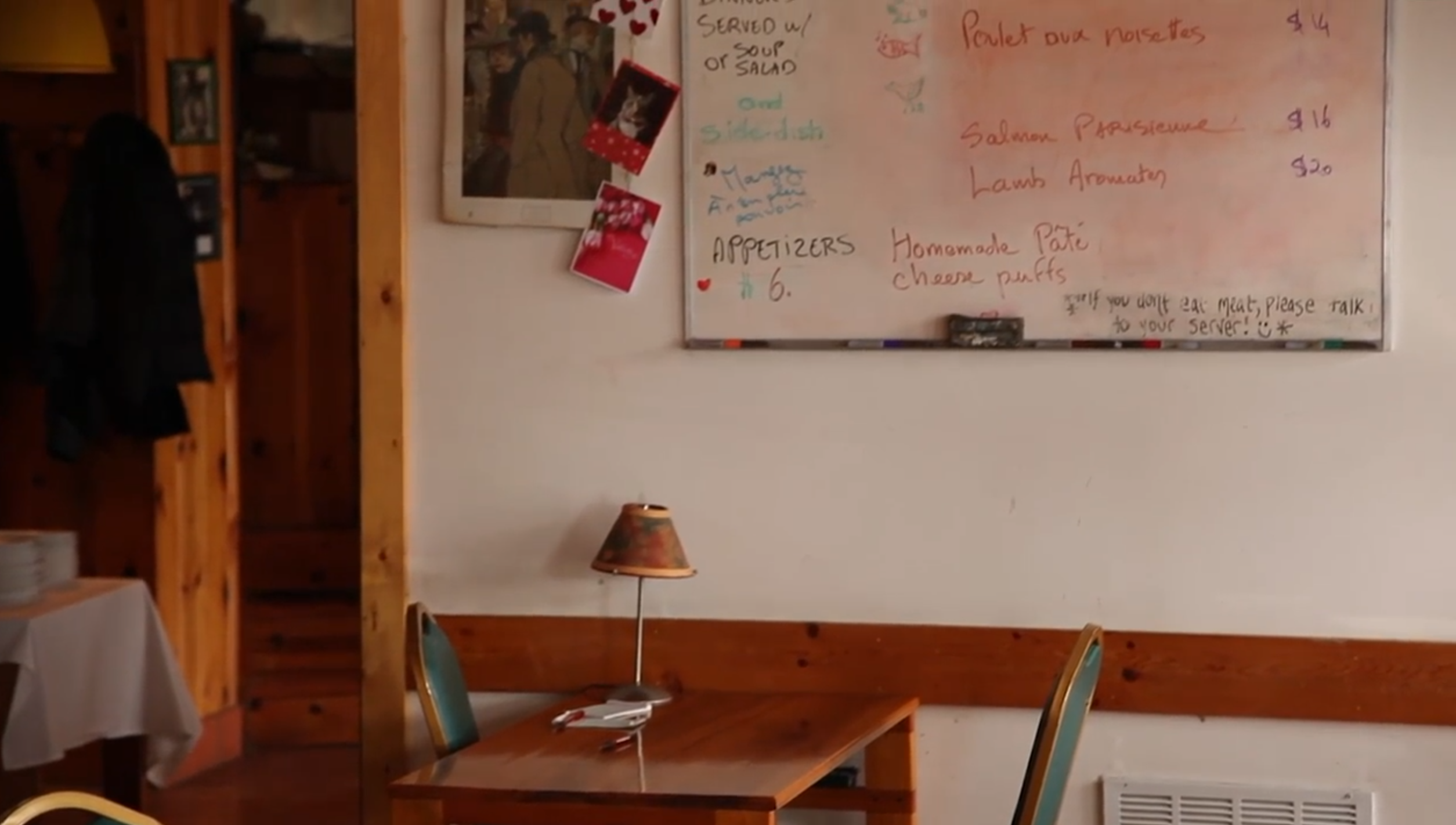 A small, unpretentious restaurant table with the menu behind on a whiteboard.