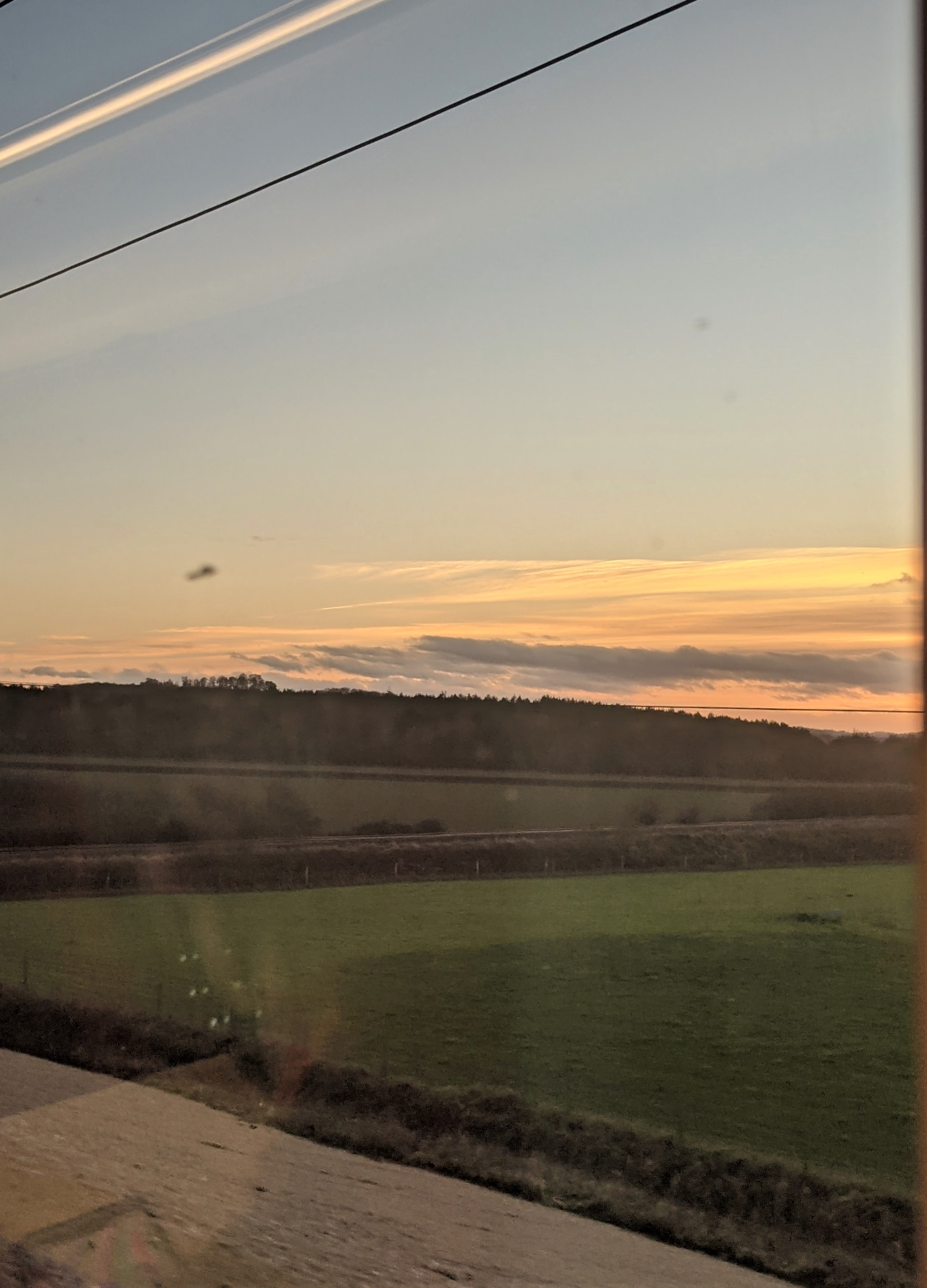 A sunset and green field seen through the train window