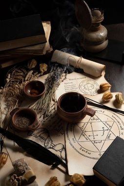 Photo of some magic spells on parchment covered with flowers and other ingredients in dark brown cups