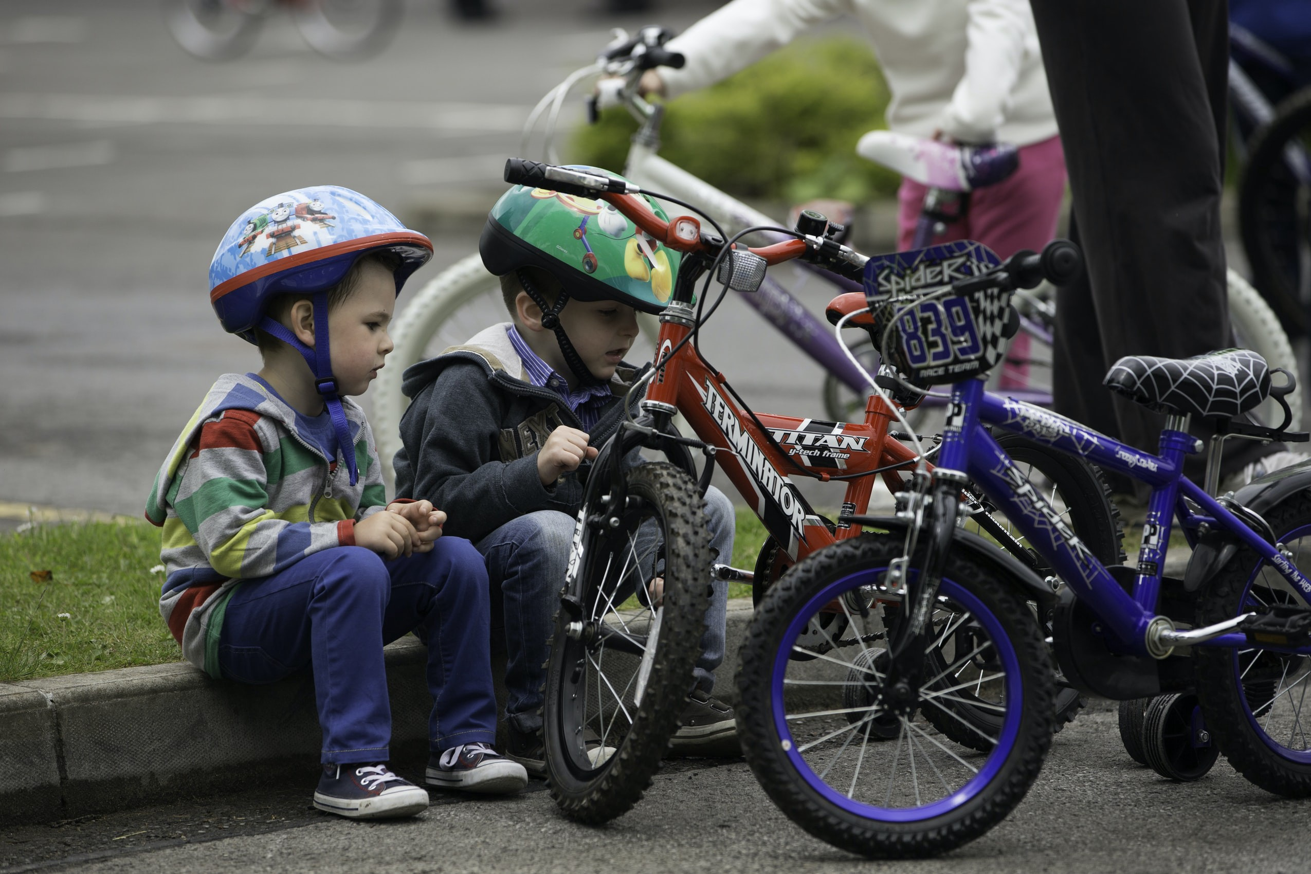 Two boys in helmets sitting on a curb next to bicycles.