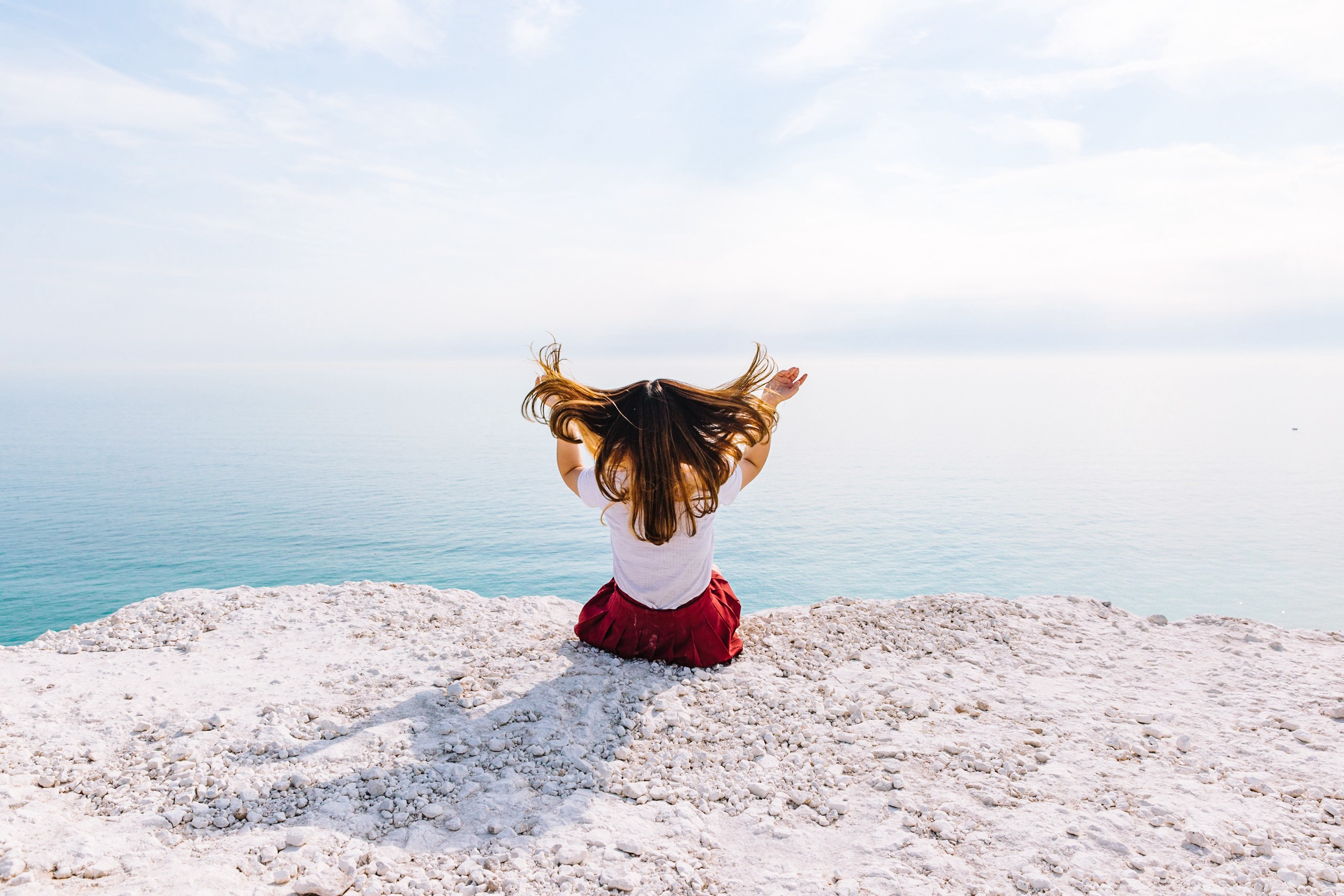 woman sitting on a cliff in front of the ocean throwing her hair