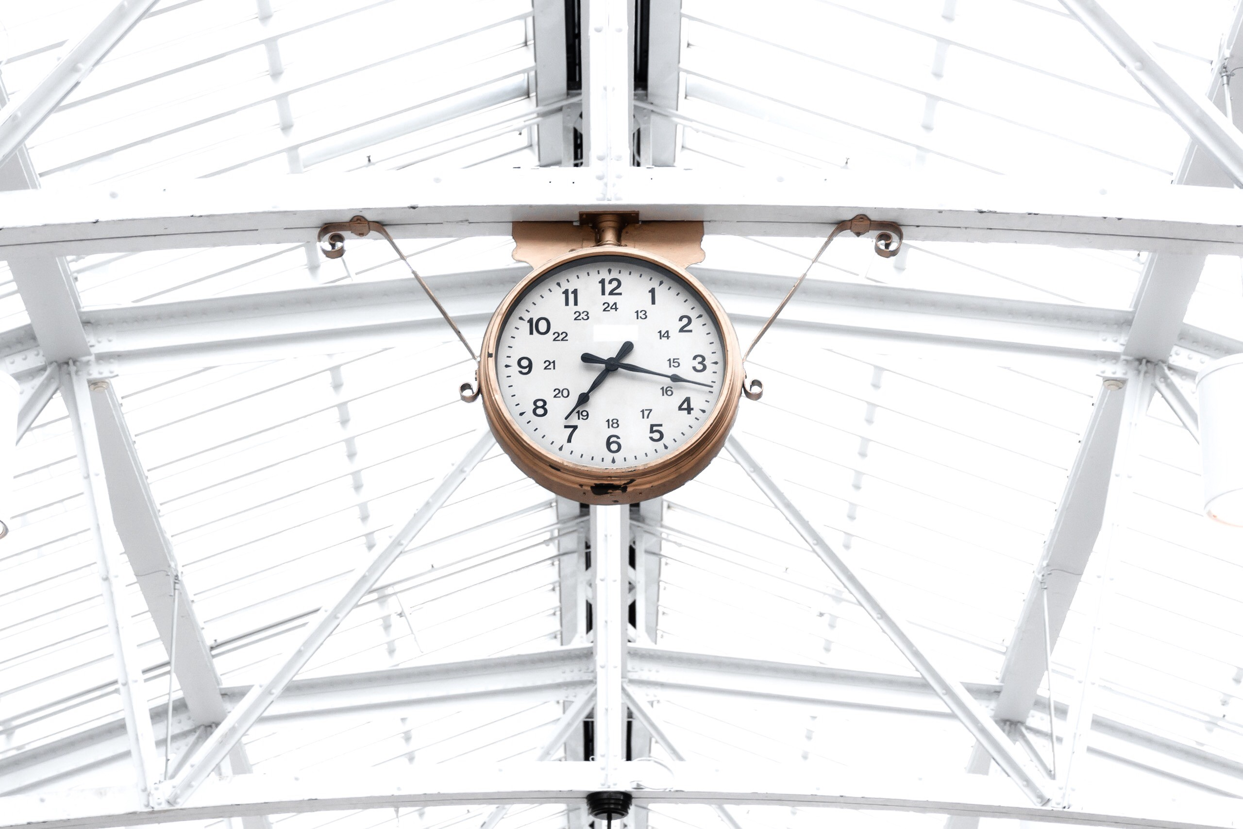 """A copper clock hung on a ceiling of white steel beams to represent Mel Robbins's """"The 5-Second Rule"""""""