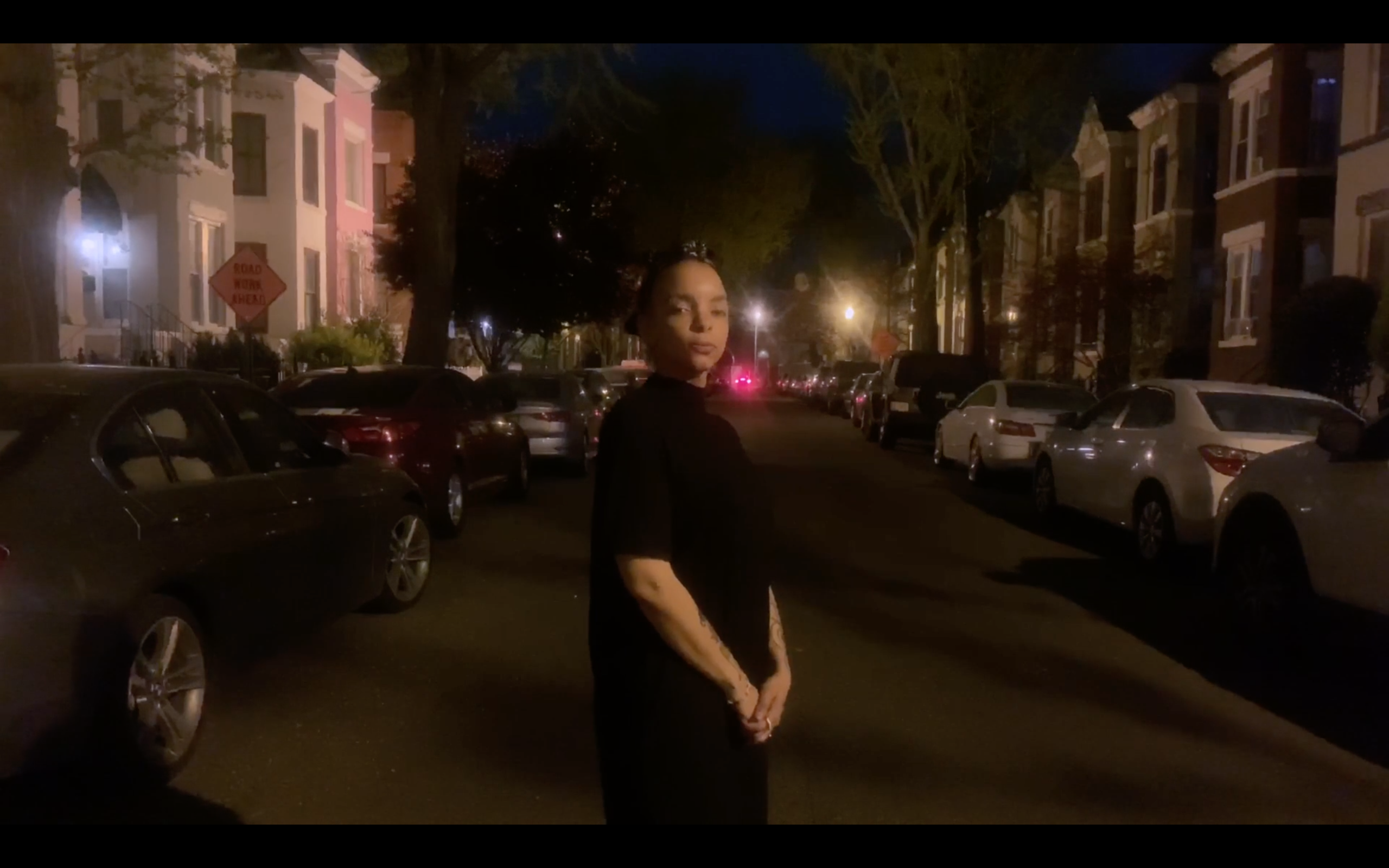 A Black woman stands on a city street at night. She flanked by parked cars part on both sides of the road, street lights lit up in the distance.