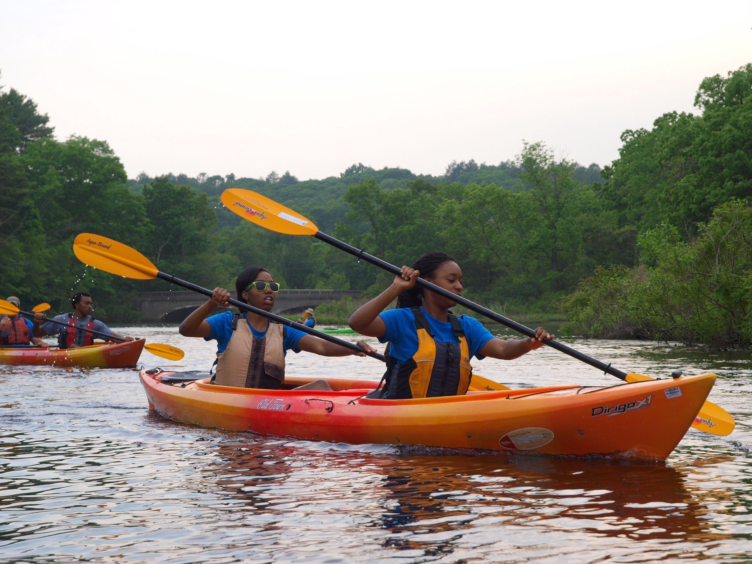 Two women wearing life vests kayak on a river.