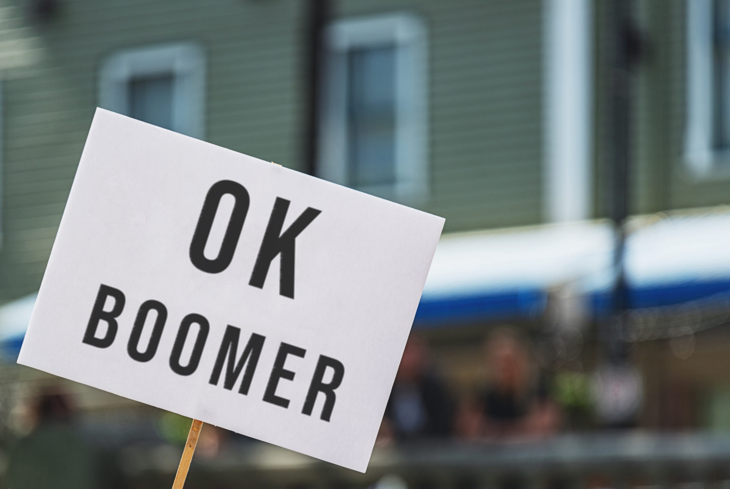 "A white protest sign with ""OK BOOMER"" written in capital letters against a blurred urban background"