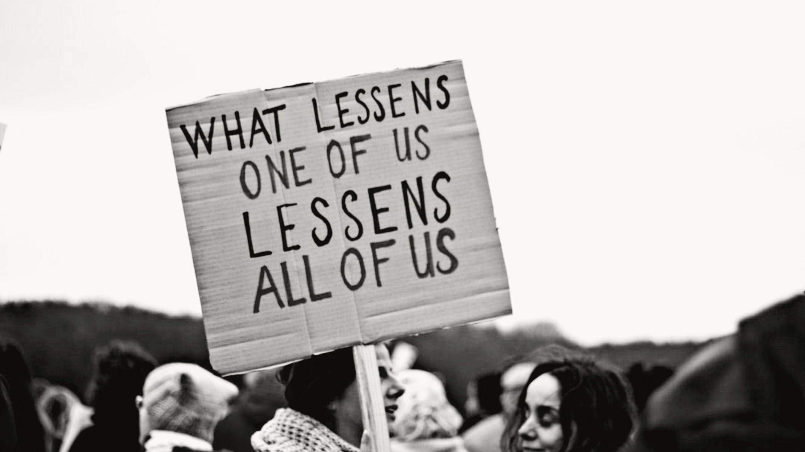 Protest sign reads 'What lessens one of us lessens all of us'.