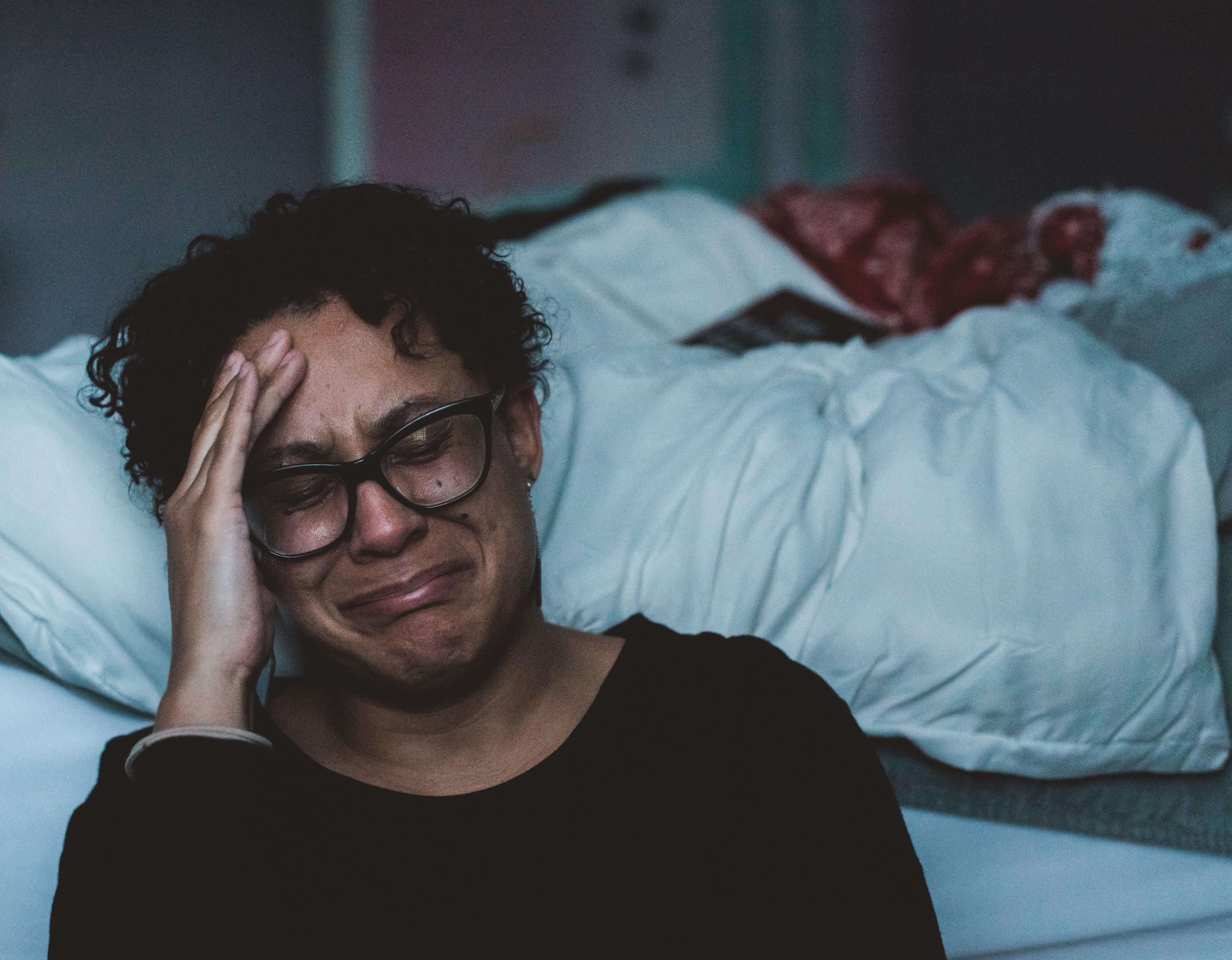 A woman sitting at bedside crying