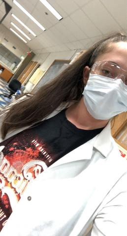 woman wearing safety glasses, a mask, and lab coat