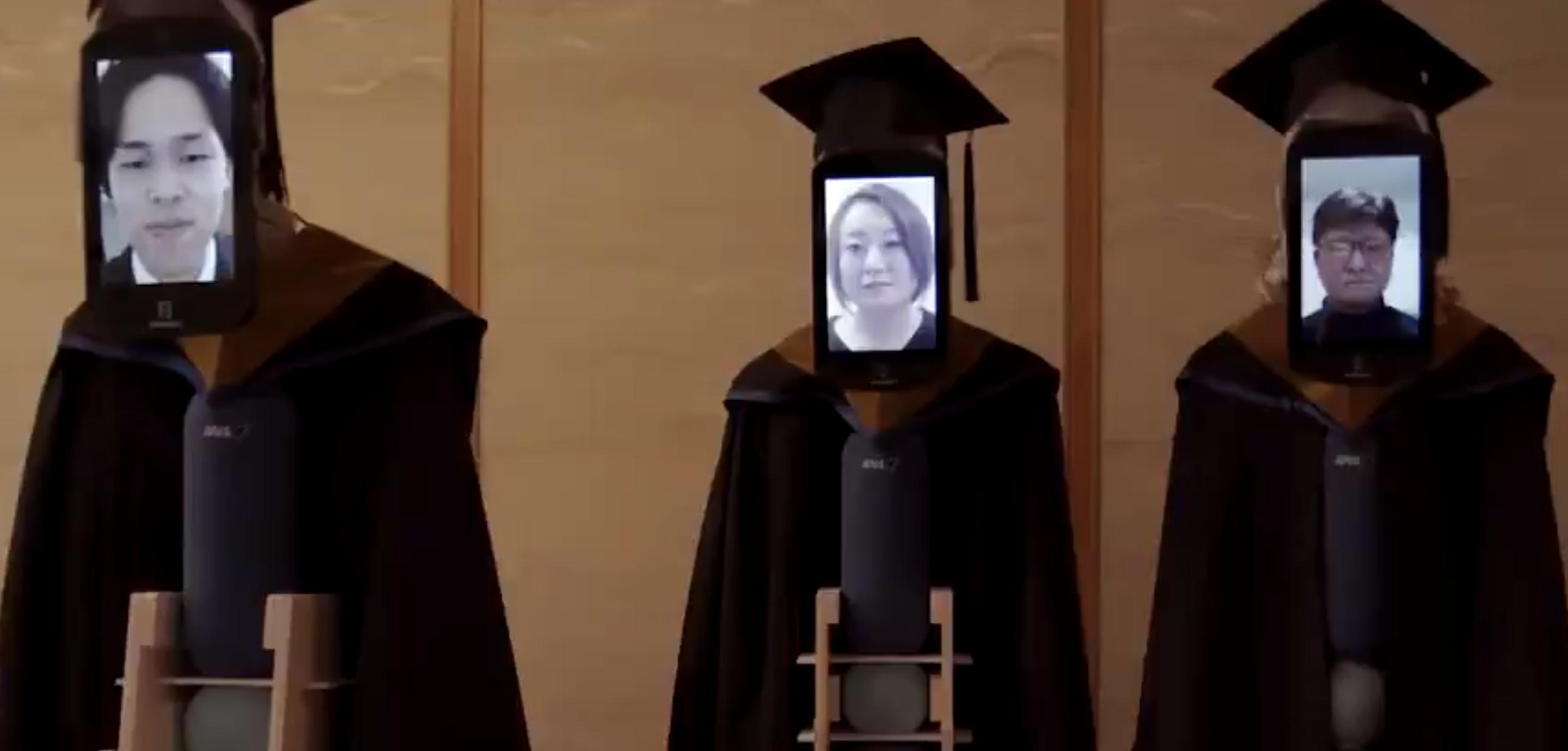 Tablets showing the faces of university students attached to telepresence robots wearings academic caps and gowns