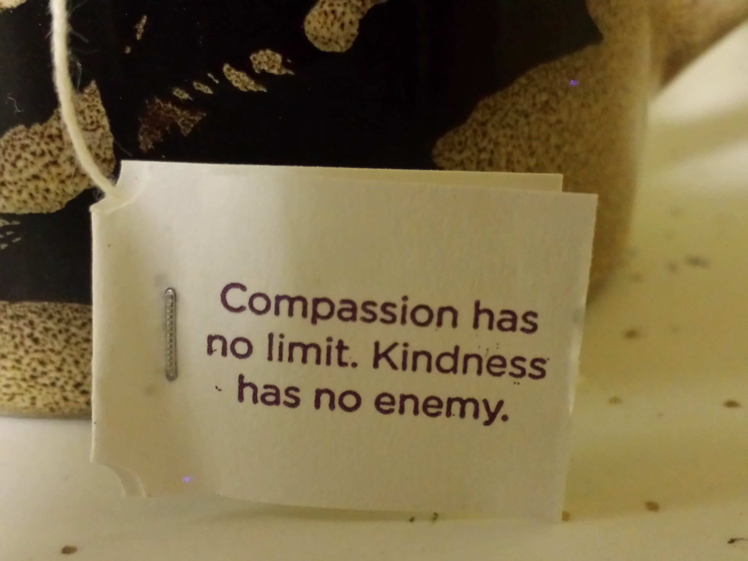 """Teabag tag reads """"compassion has no limit. Kindness has no enemy."""""""