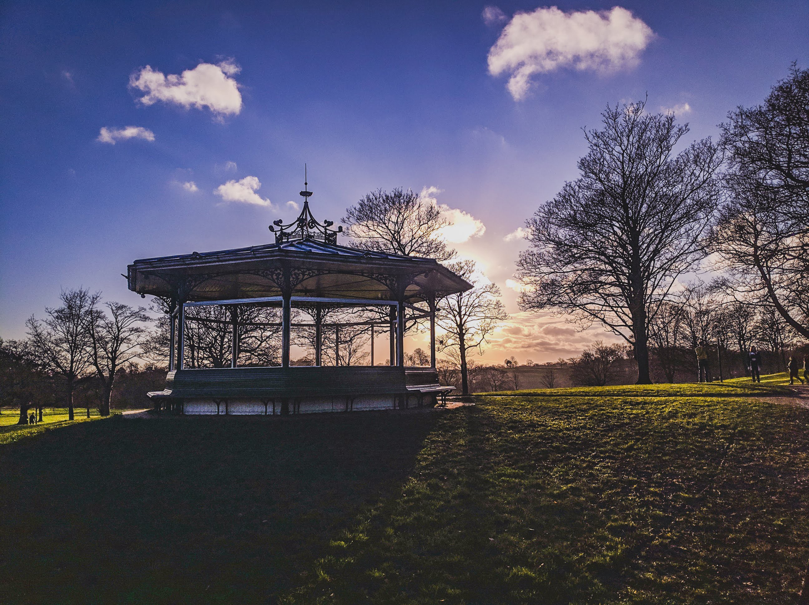 An empty bandstand is silhouetted against blue skies and winter trees on a sunny day in the park