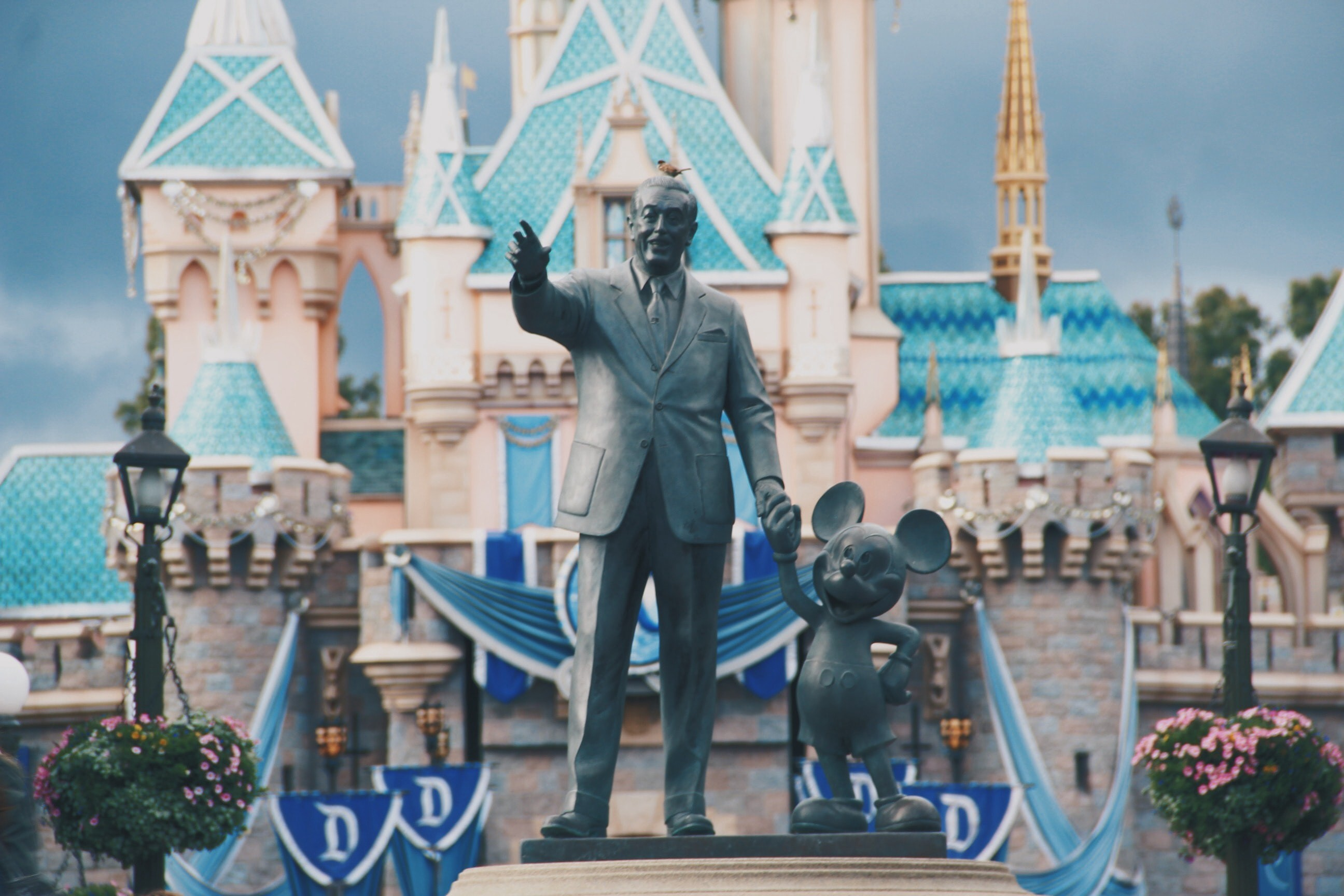 A color photo of a statue of Walt Disney holding hands with Mickey Mouse.