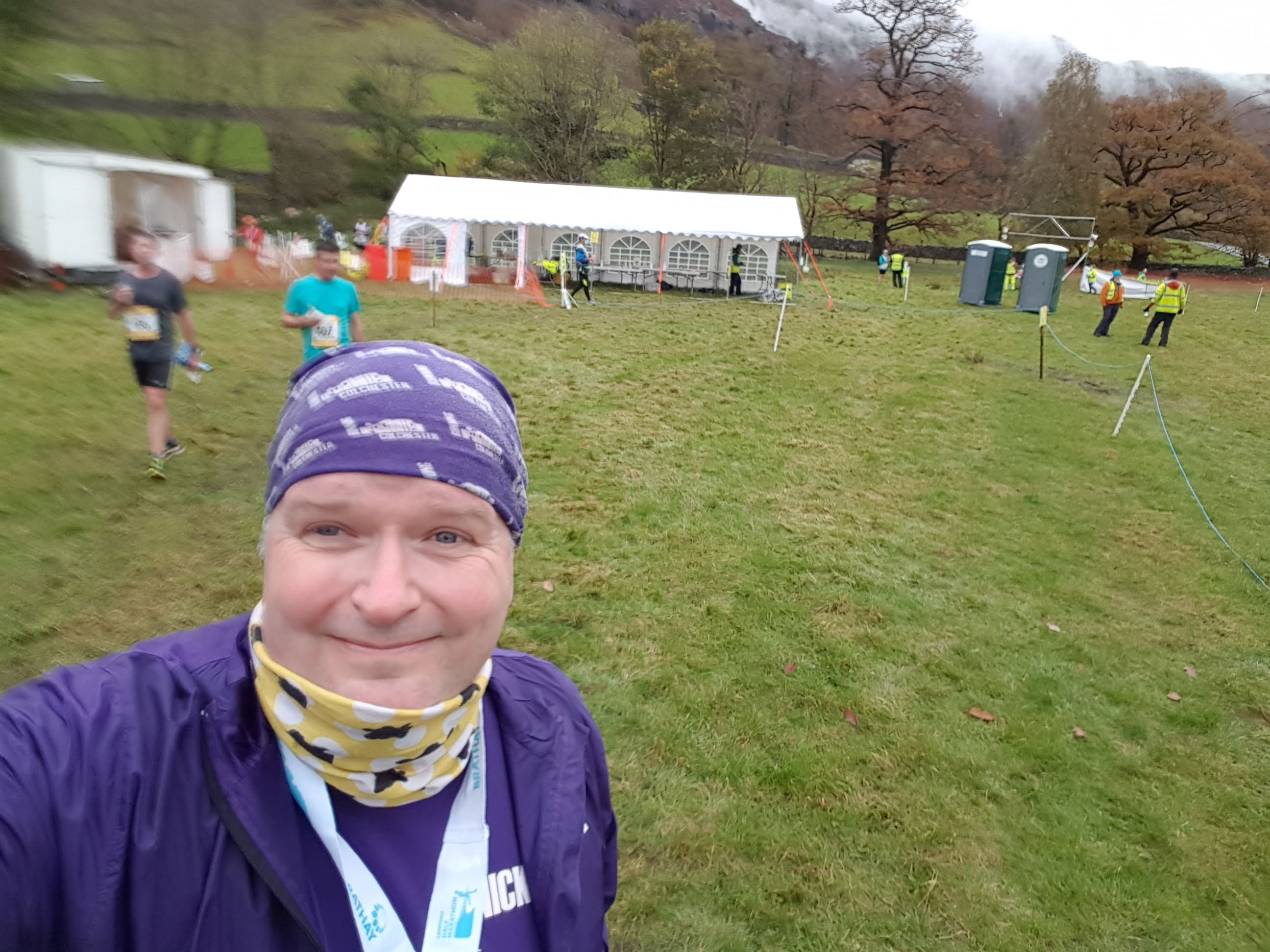A selfie of a man (the author) in a purple bandanna and jacket in a field with a marquee and a pair of other runners.