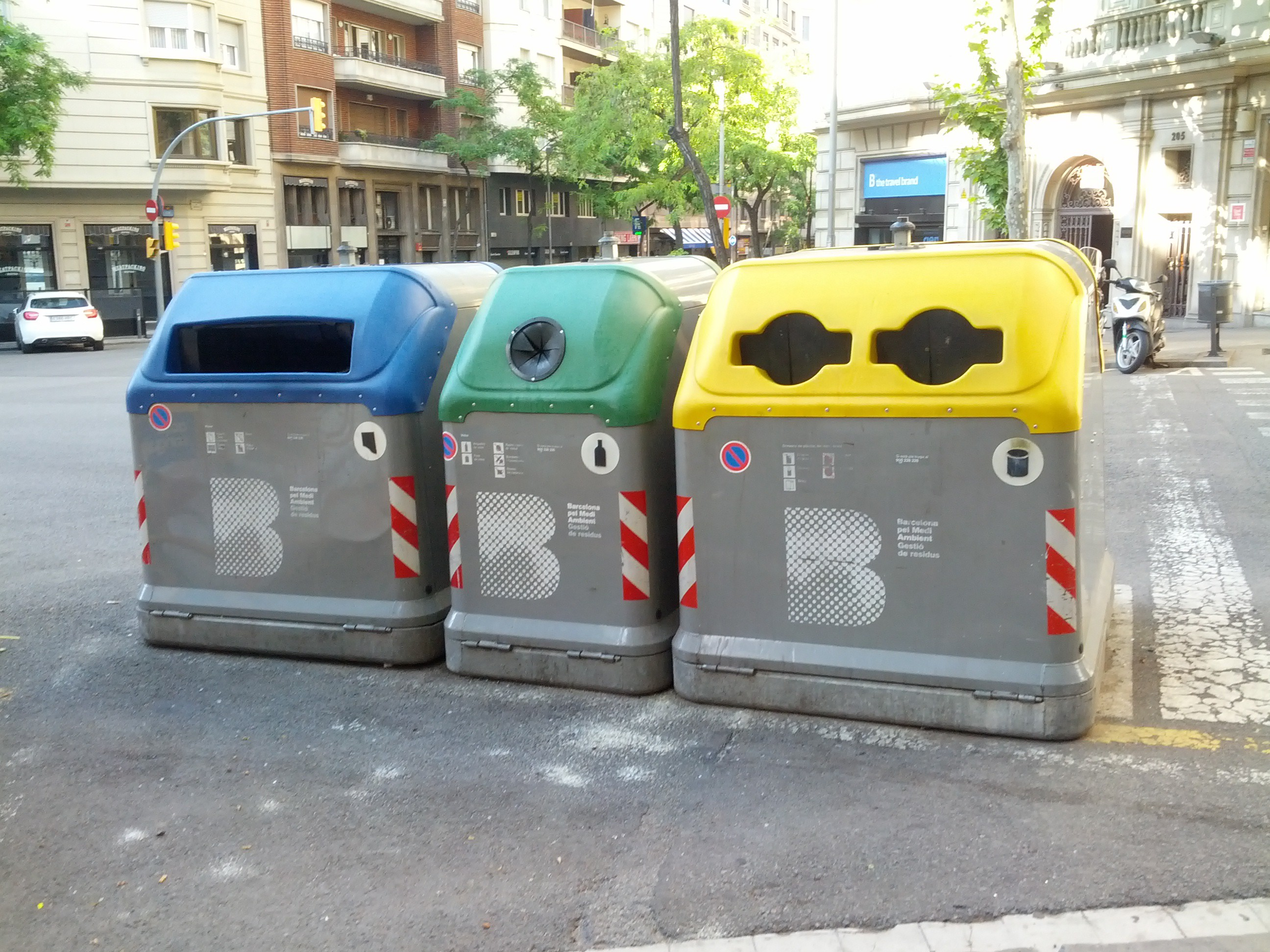 Three waste bins on the streets of Barcelona. These bins have sensors that alert city officials when they've been emptied.