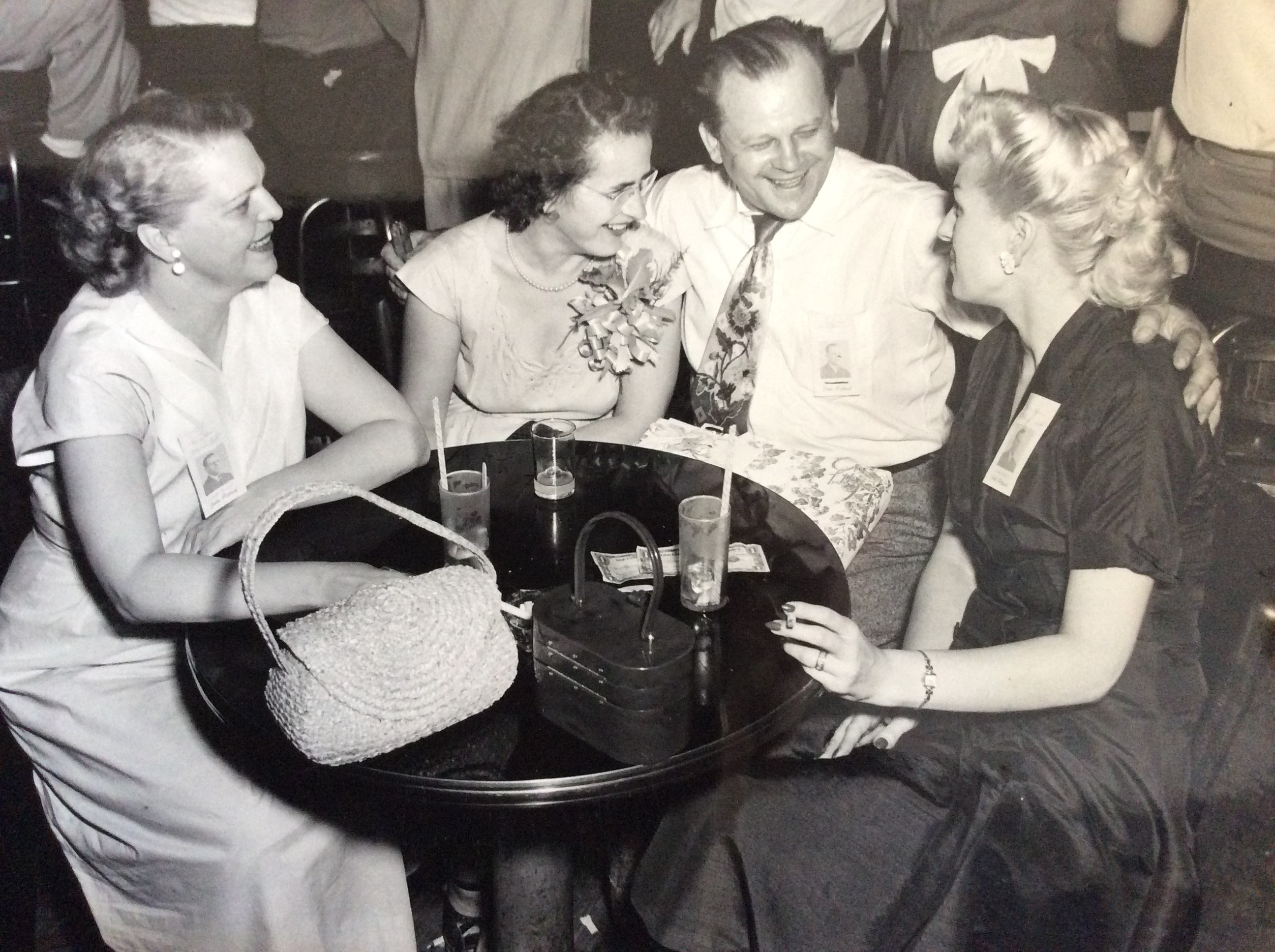 A group of people sitting around a table in a bar, laughing and talking