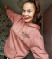 """A white woman with her long brown hair in a ponytail is smiling at the camera. She is wearing a rose pink hoodie with the words """"Just Ausome"""" writer in black."""