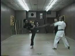 A low resolution frame showing a man in black sparring with someone in white, they are in a small martial arts dojo room.
