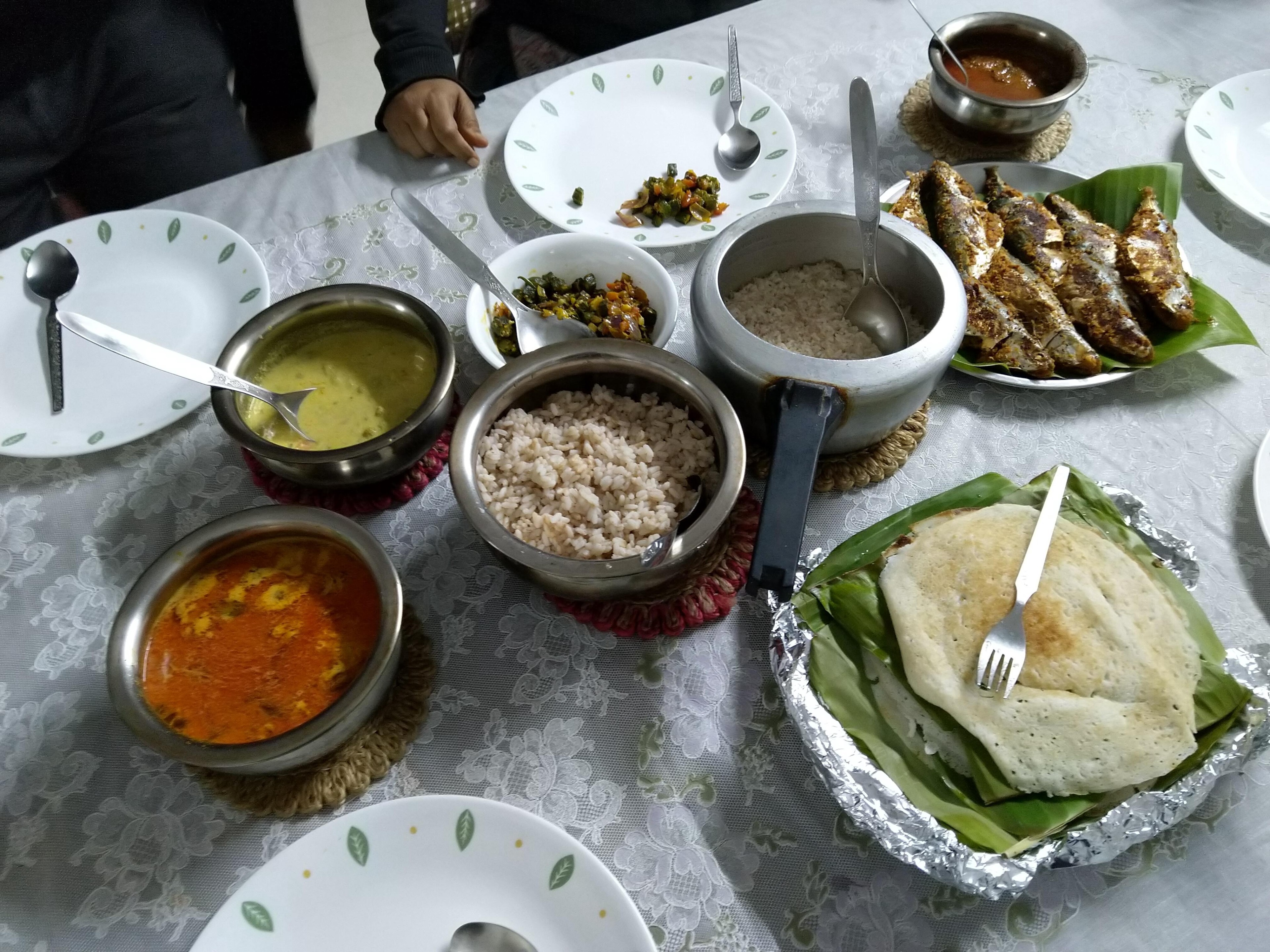 A South Indian fish meal with curries, rice, appams and fried fish