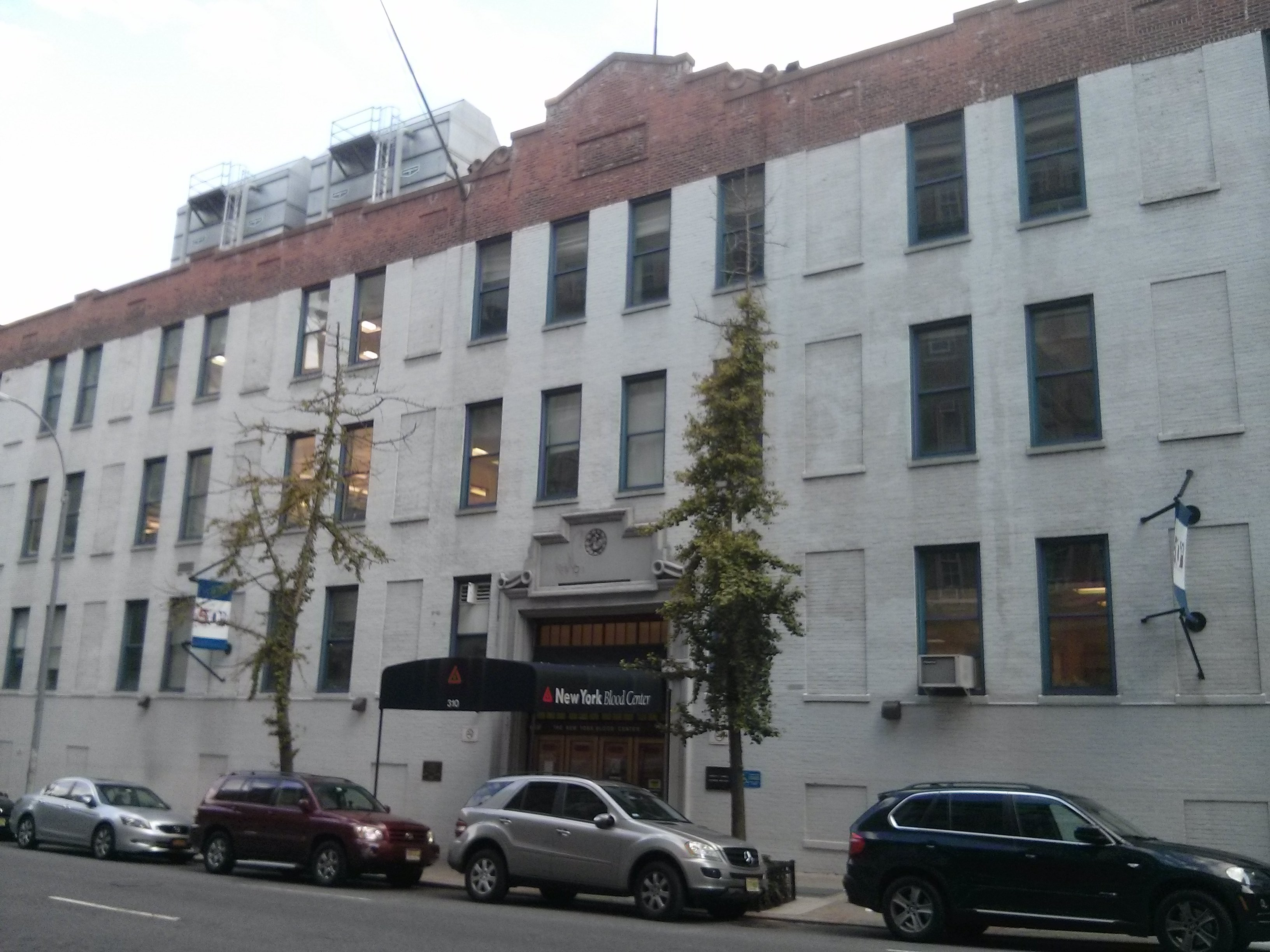 A gray four story building on the outside.