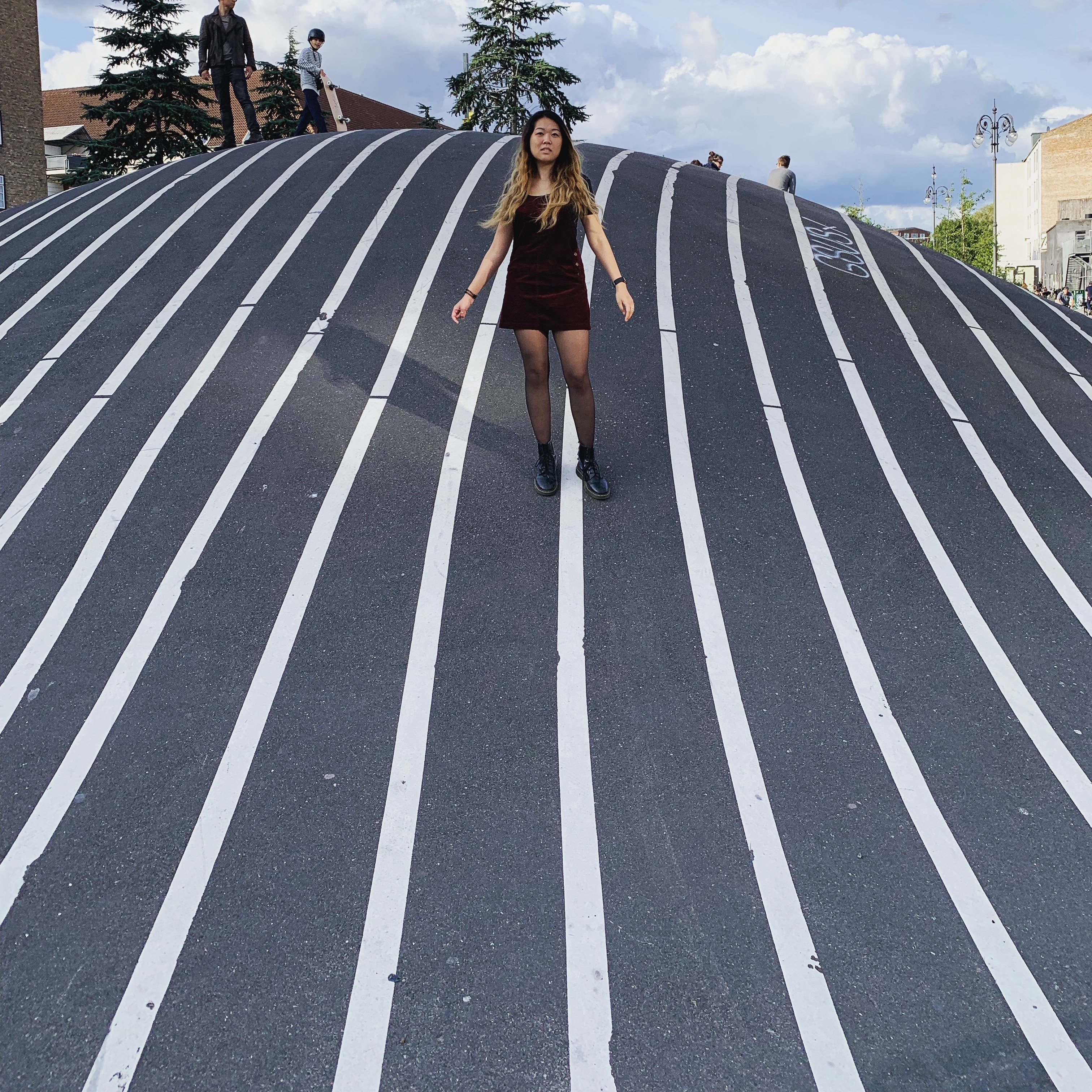 Girl standing on hill made of pavement with vertical white lines