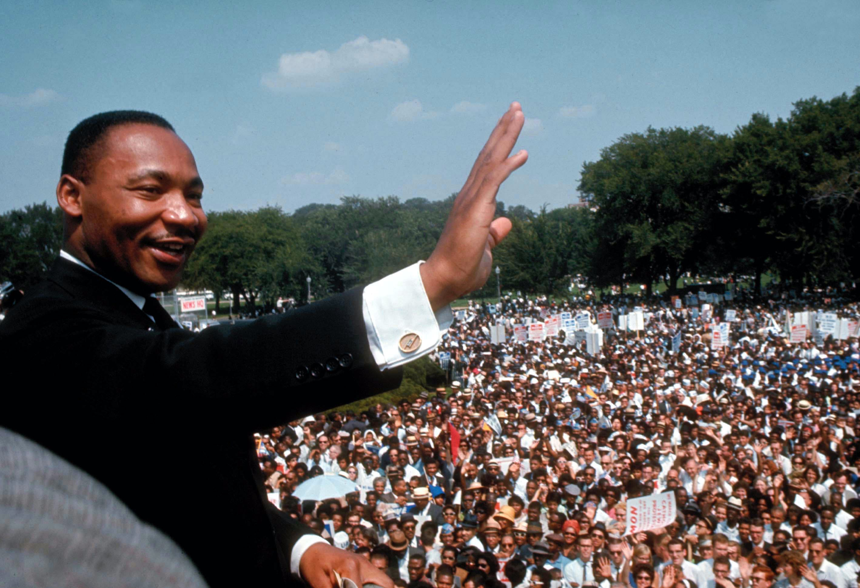 Dr. Martin Luther King Jr. smiling and waving to the crowd gathered at the March on Washington