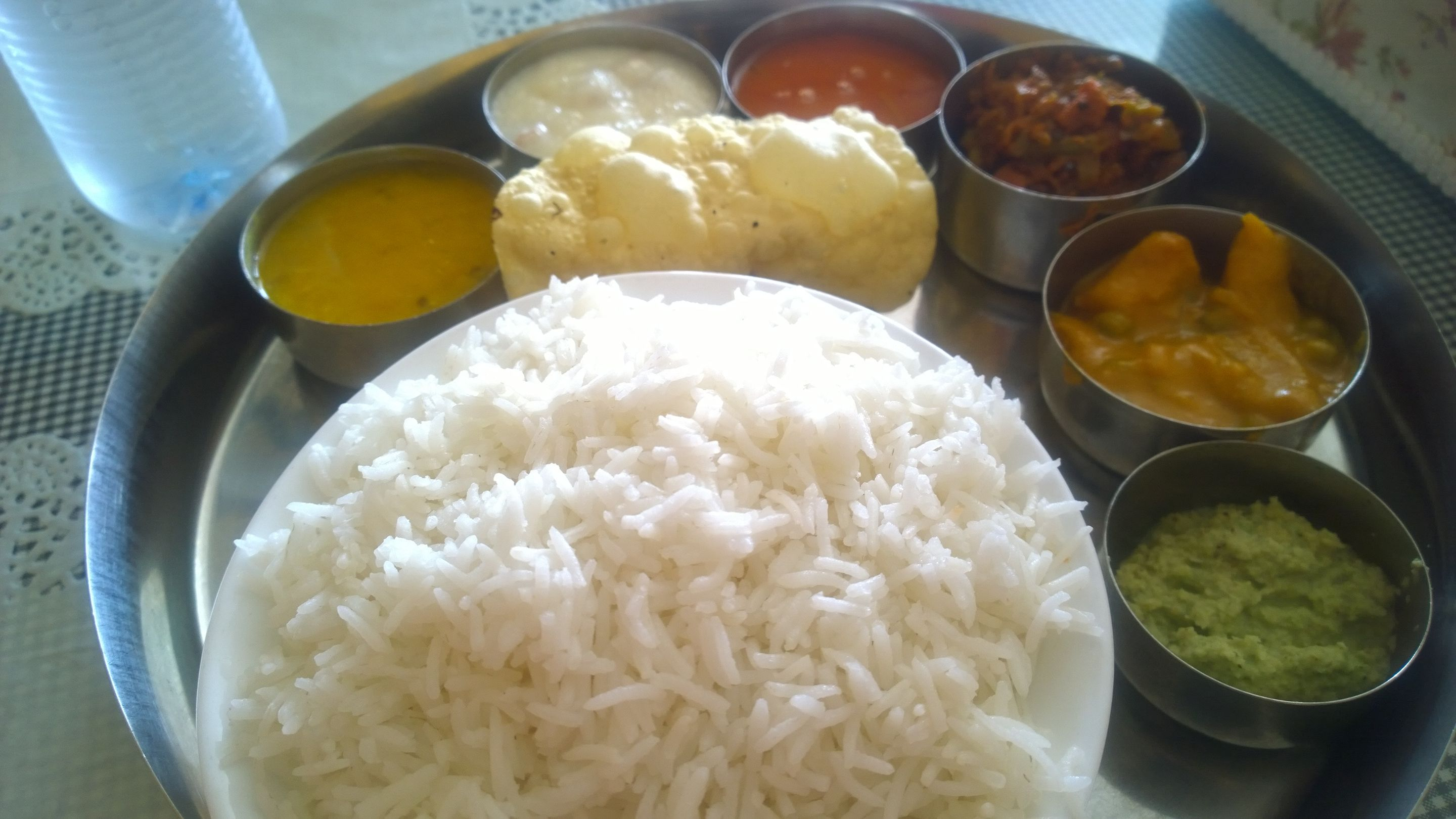 A photograph of a 'thali' with a large plate with many small bowls for dal (pulses), curries, sabzis (dry vegetable dishes), and dahi (curd).