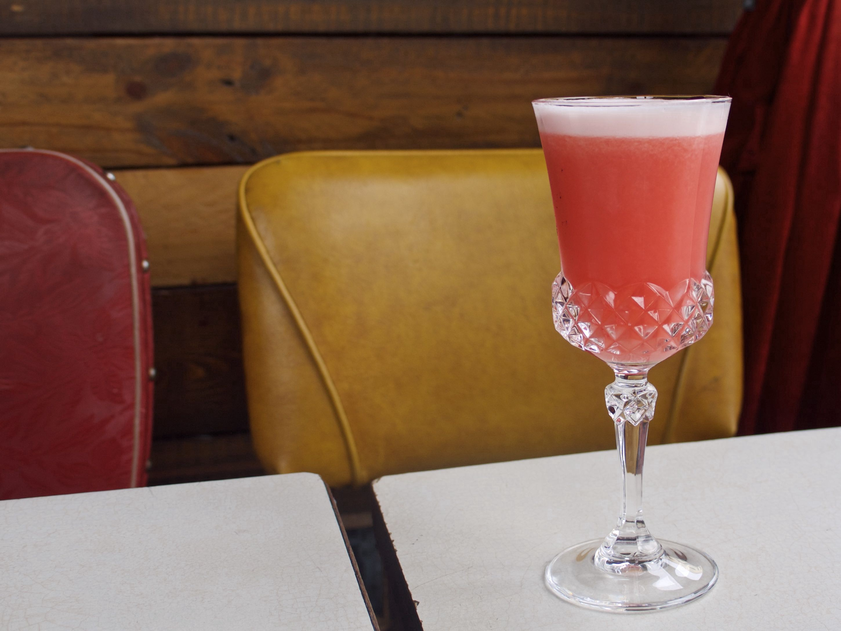 A pink drink in a coupe glass, with a layer of foam on top.
