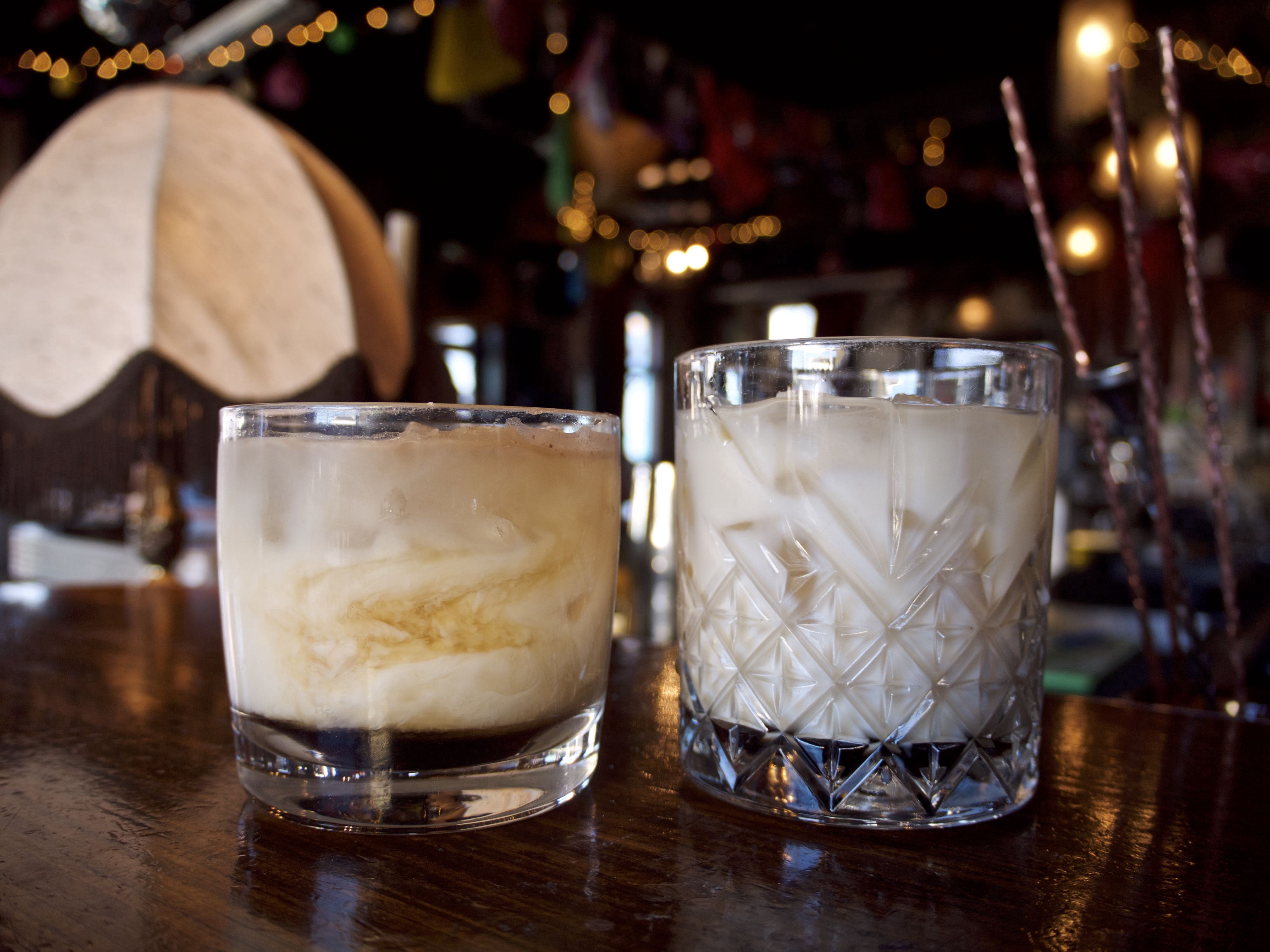 Two White Russians in short glasses on a table in a bar.