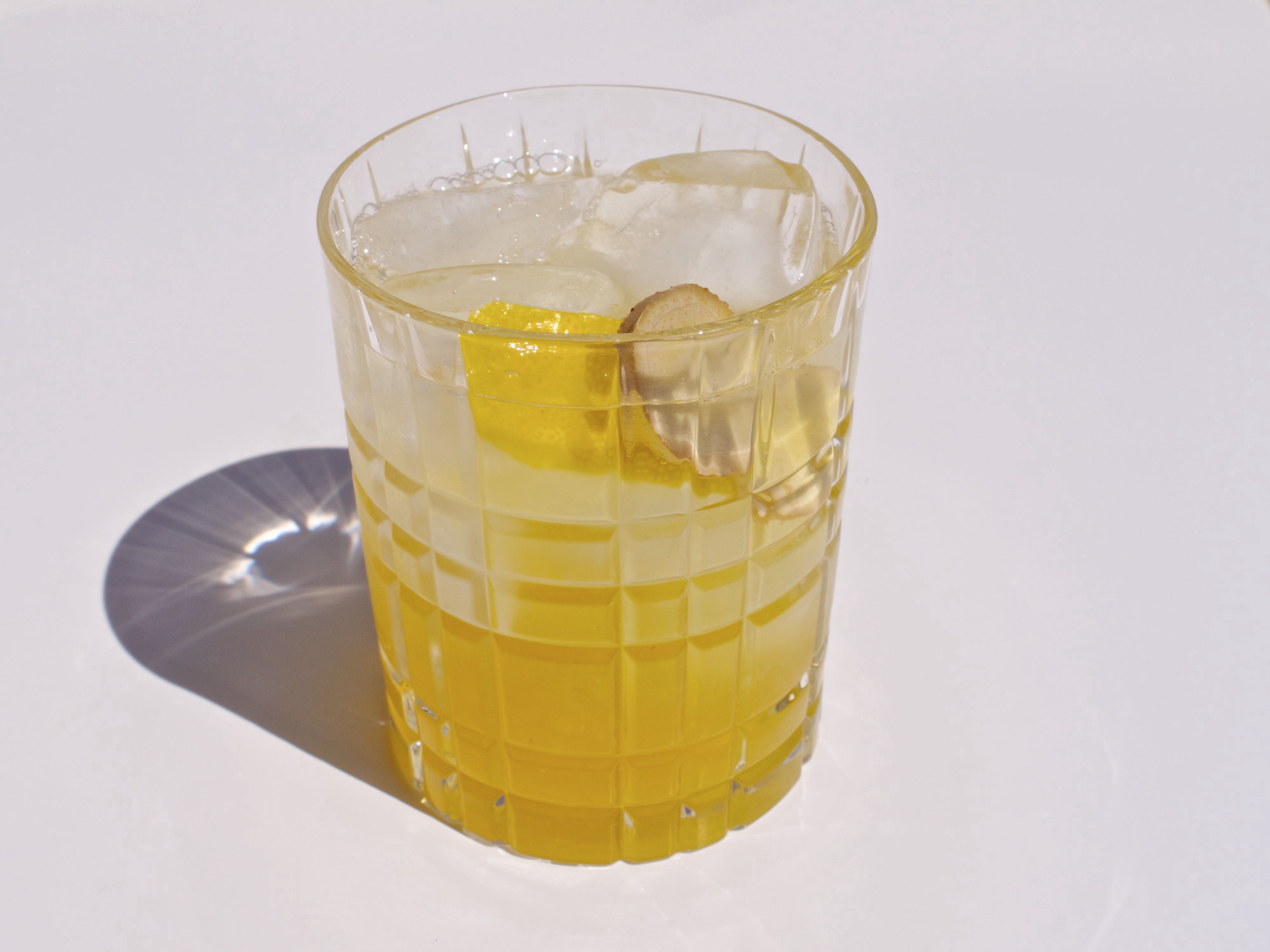 A transparent yellow drink with ice cubes on a white surface. A strong light source causes the glass to cast a shadow.