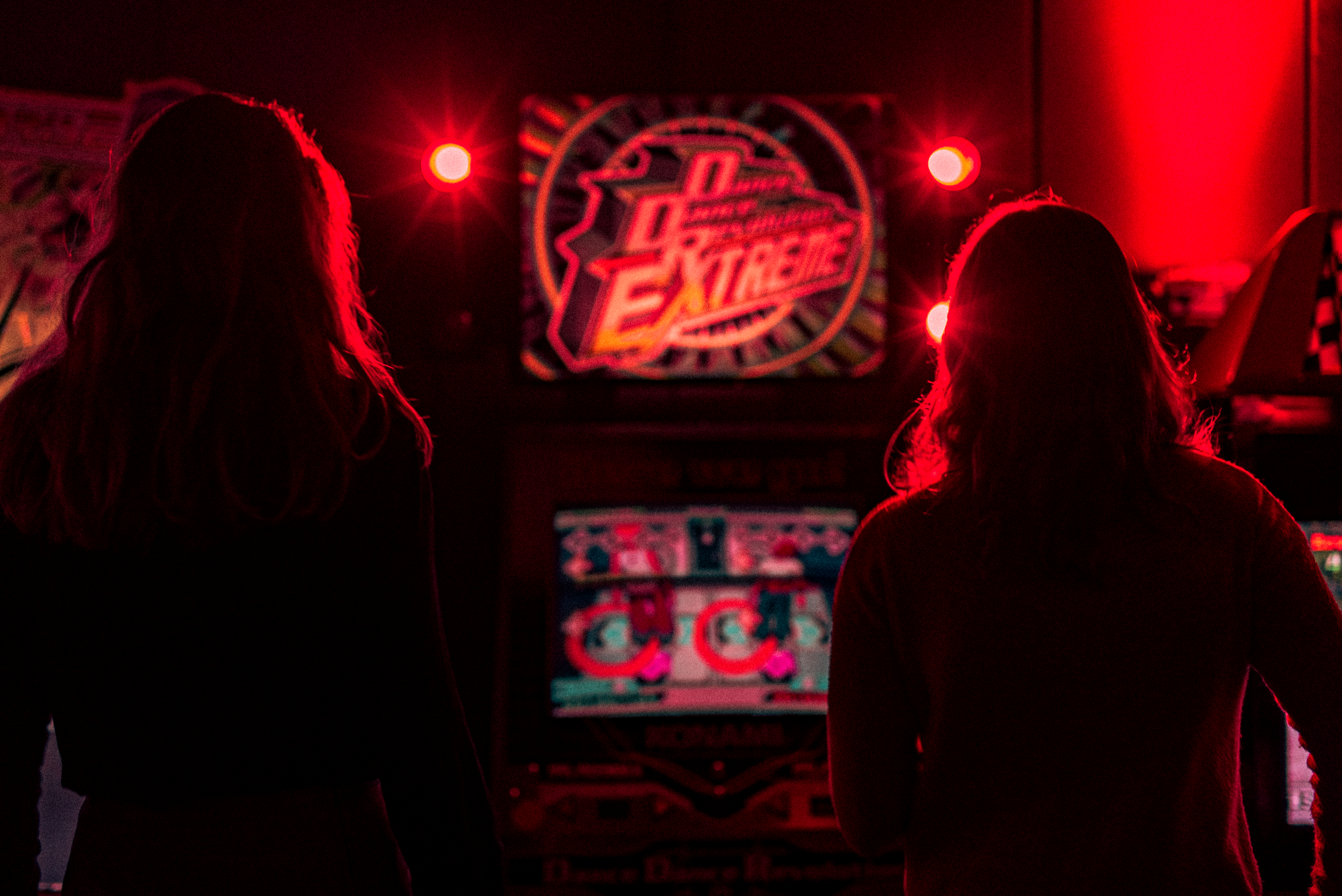 Two women's silhouette playing dance dance extreme at an arcade