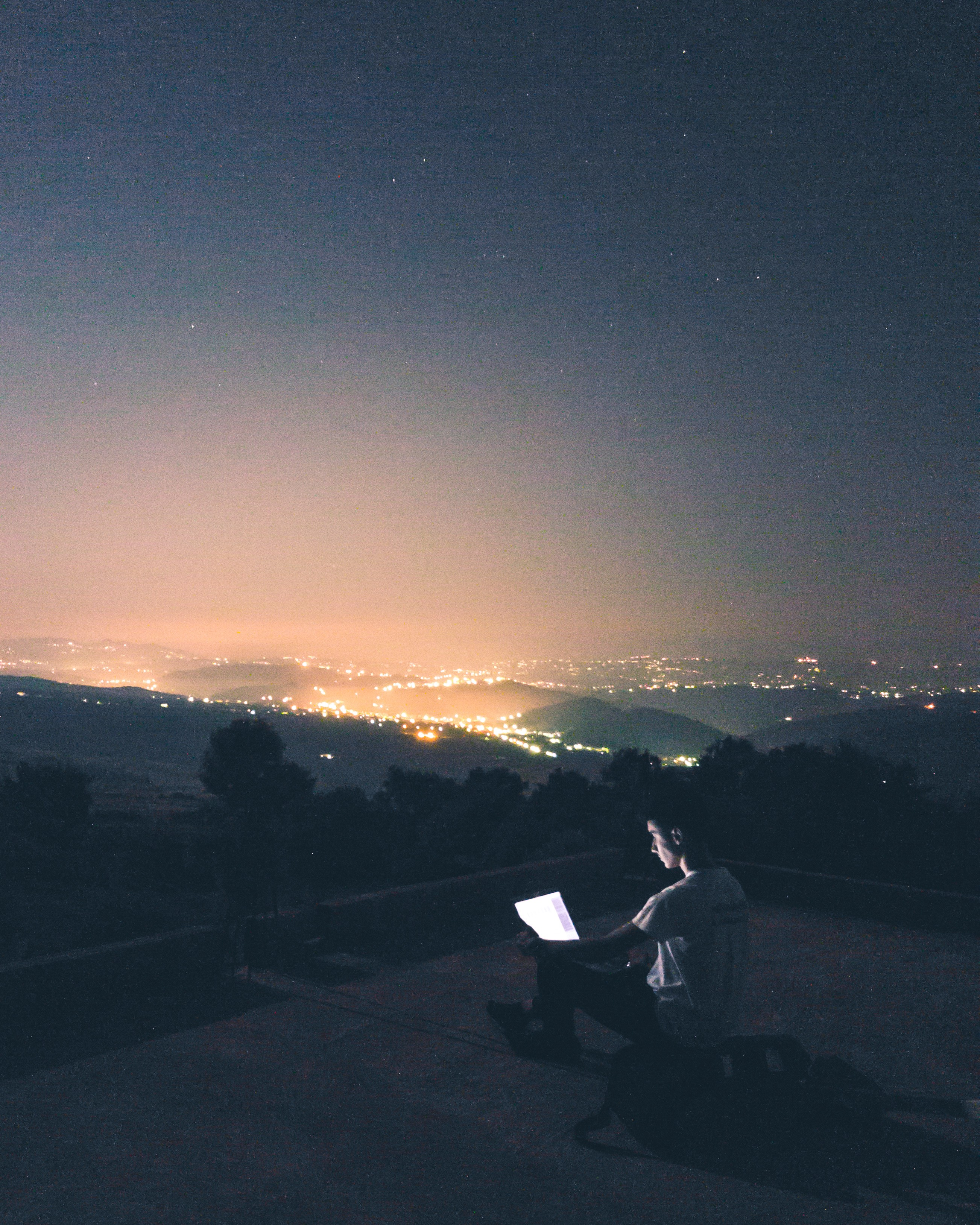 Young white male sitting on a lonely hill with a laptop at night. City lights glare in the far distance.