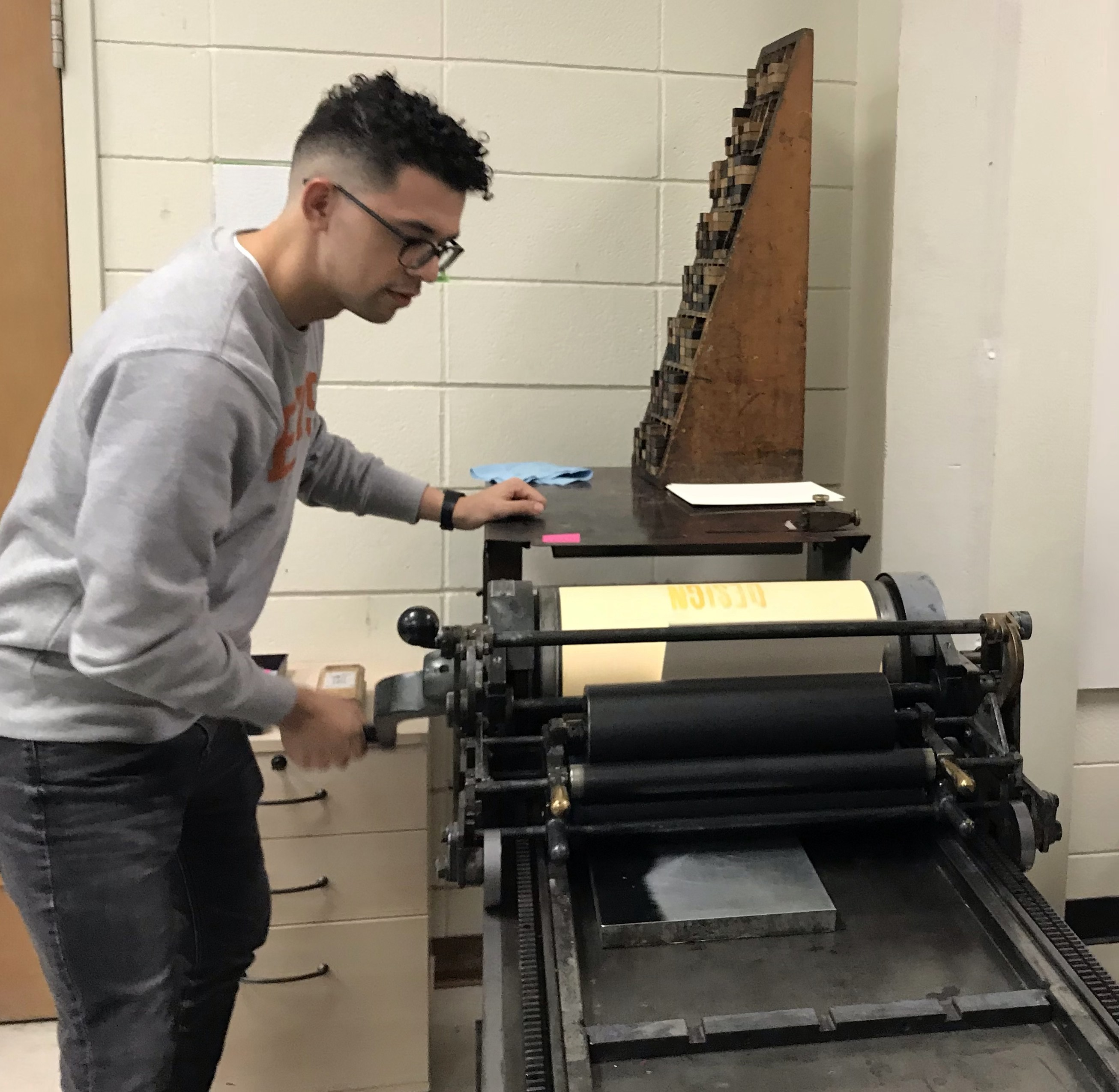 """UT Theatre & Dance graduate student works a letter press in a """"Greeting Cards from the Anthropocene"""" workshop."""