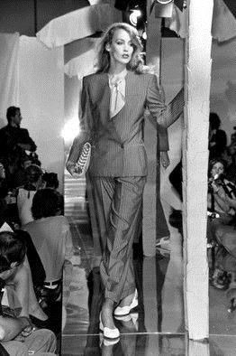 In black and white: a female runway model wearing a suit and flats.