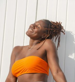 Black woman with locs smiling under sun in orange top