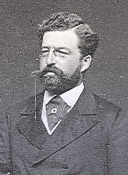Philip dressed in a suit and cravat. He has dark curly hair and a long mustache. He's wearing a monocle.