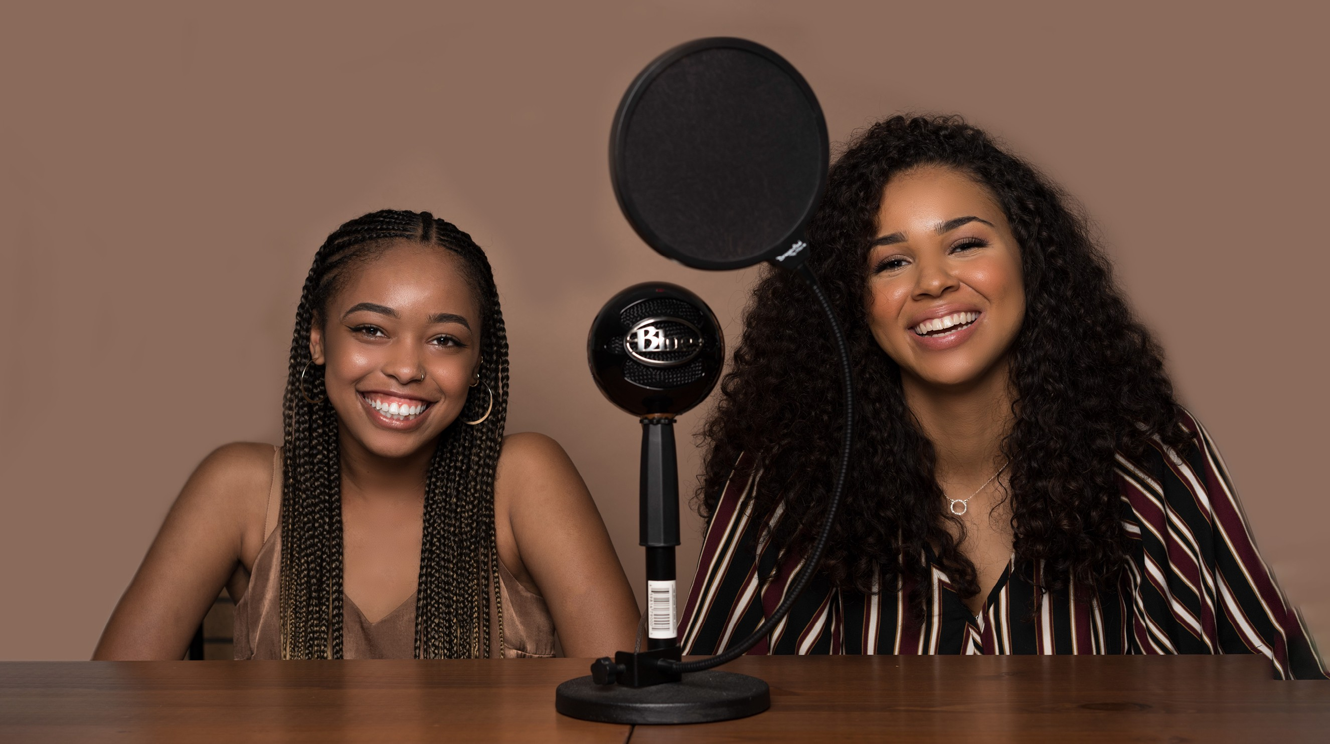 Sydney Charles and Tatum Larsen sit behind a wooden table smiling. On the table between the two of them is a microphone.
