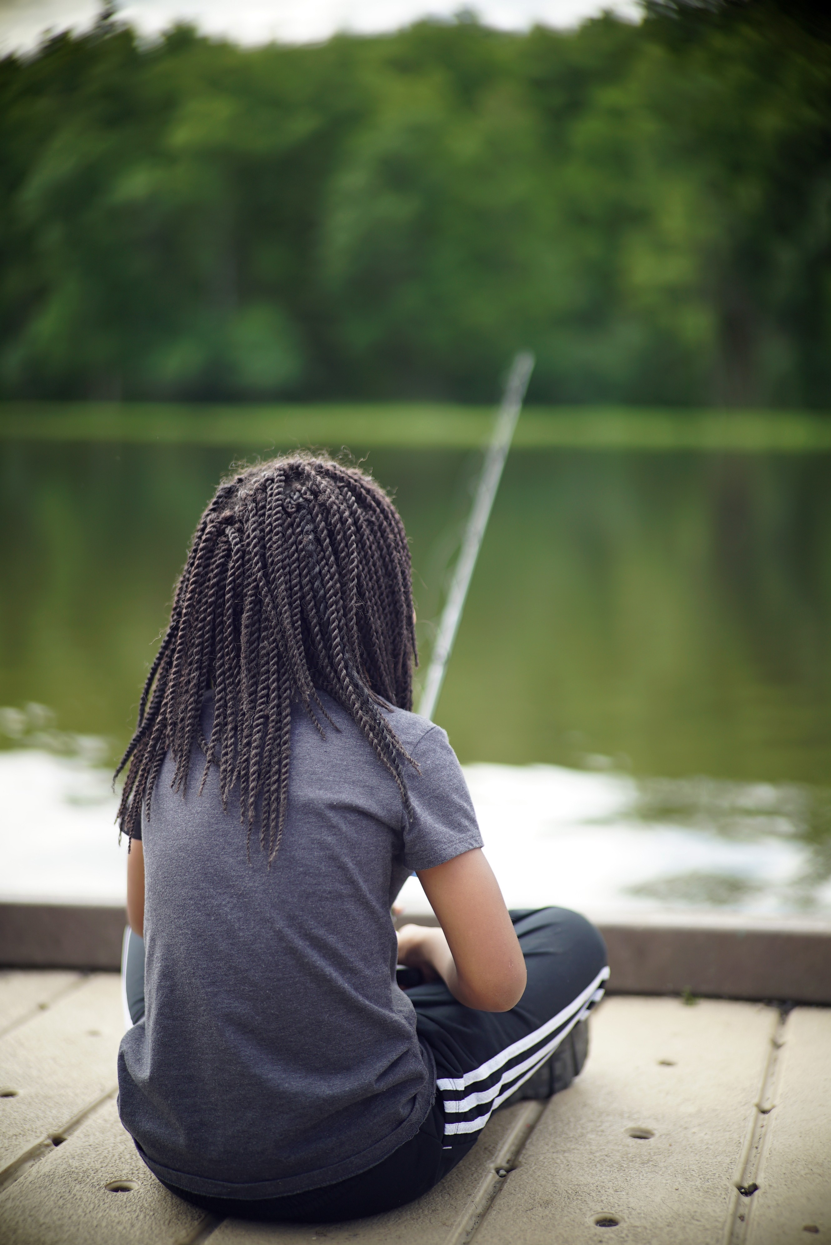 Young girl sitting on a dock fishing