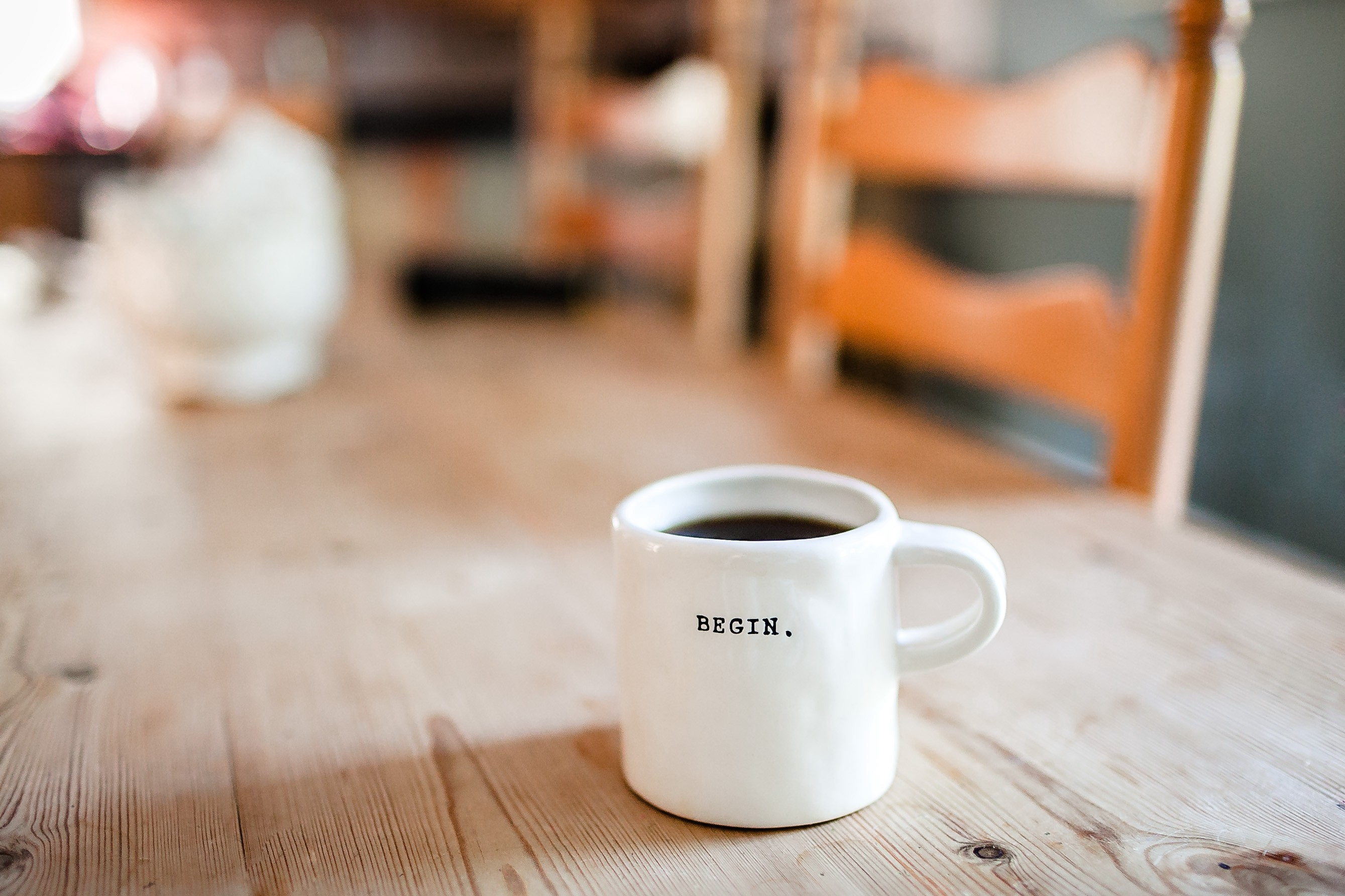 """White, filled coffee mug with text """"BEGIN."""" on it, on a wooden table."""