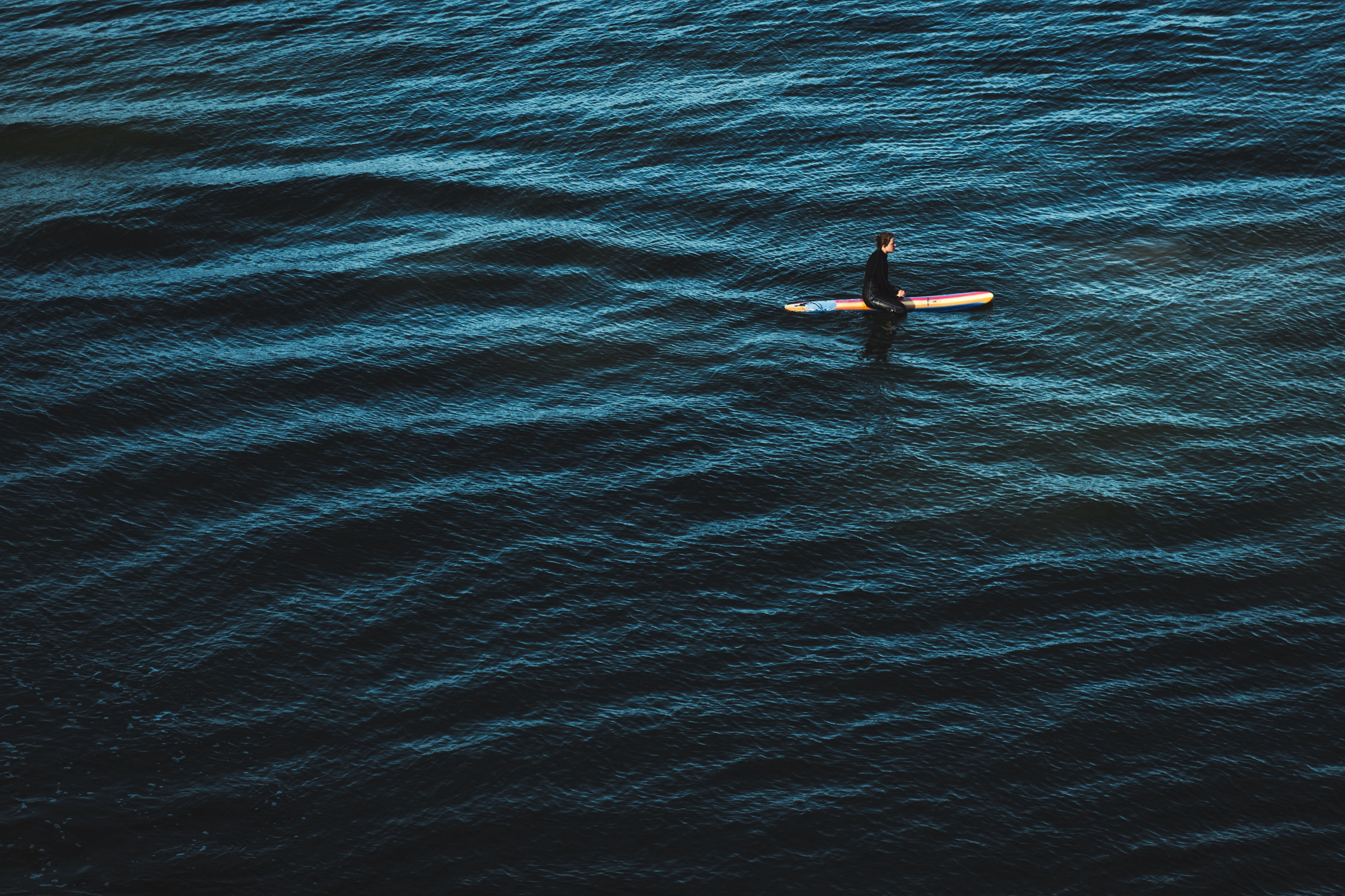 Photograph of the ocean. A person is sitting on a paddle board, waiting for a wave.