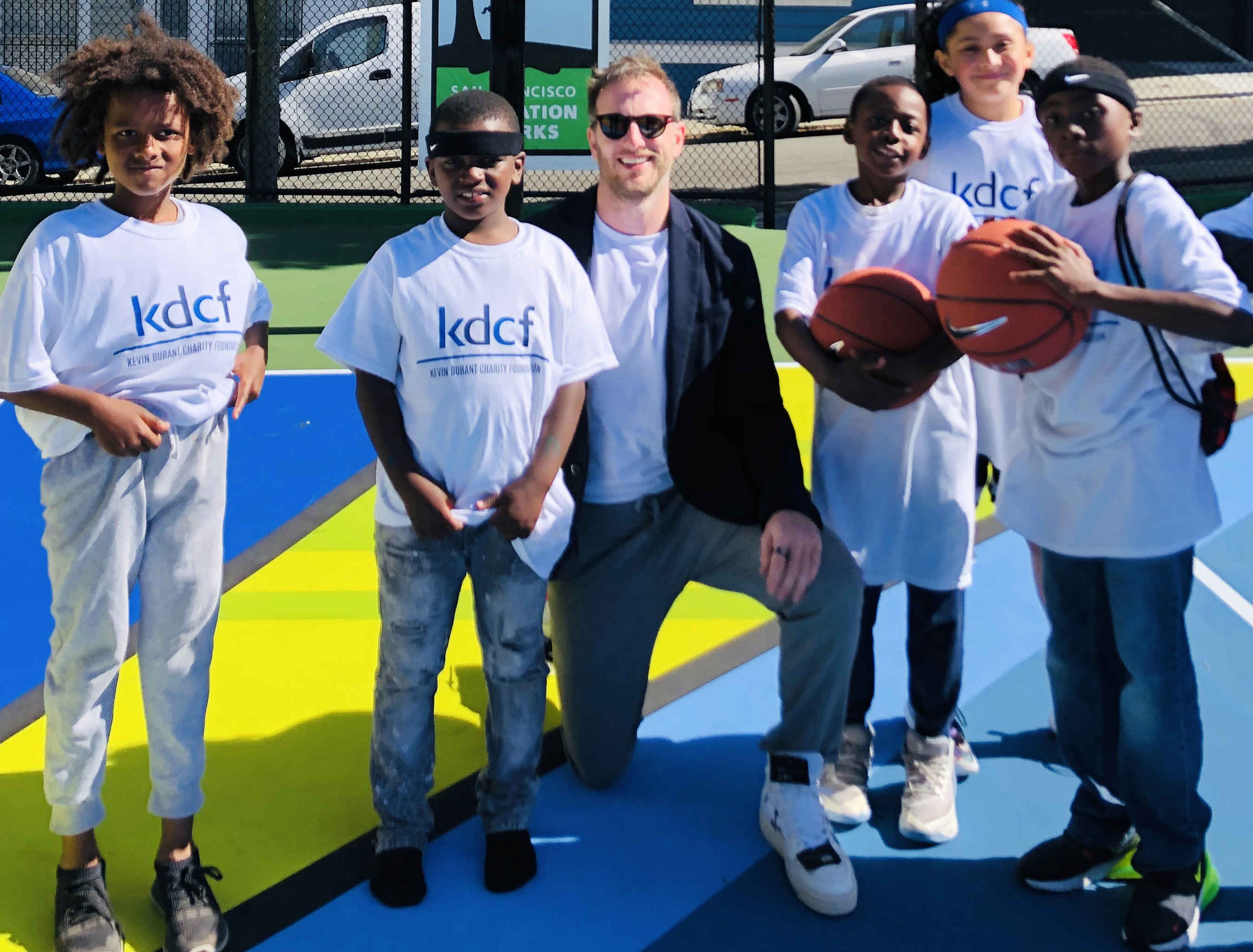 Joe with local youth basketball players at the court opening.