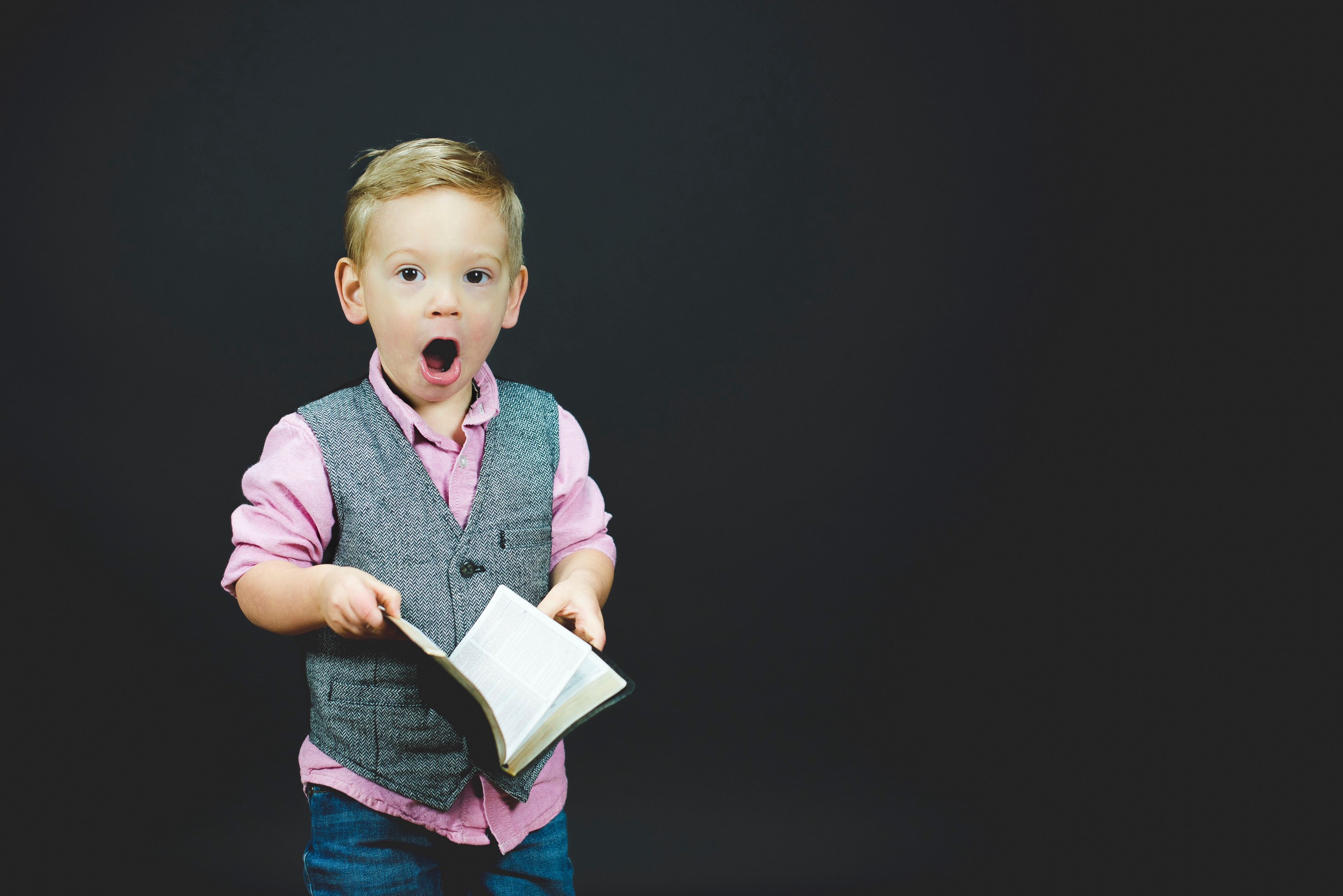 surprised little boy holding a book