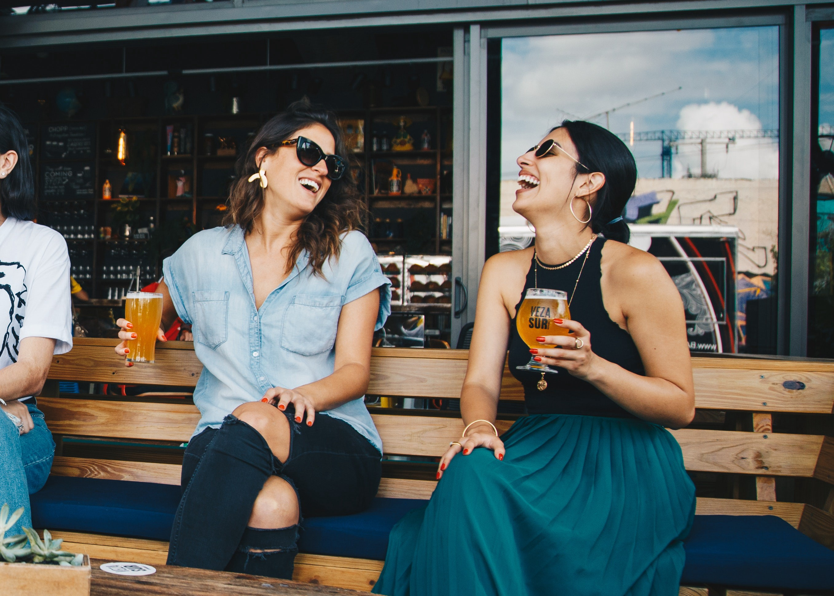 Two Smiling Women Sitting on Wooden Bench Drinking a Beer