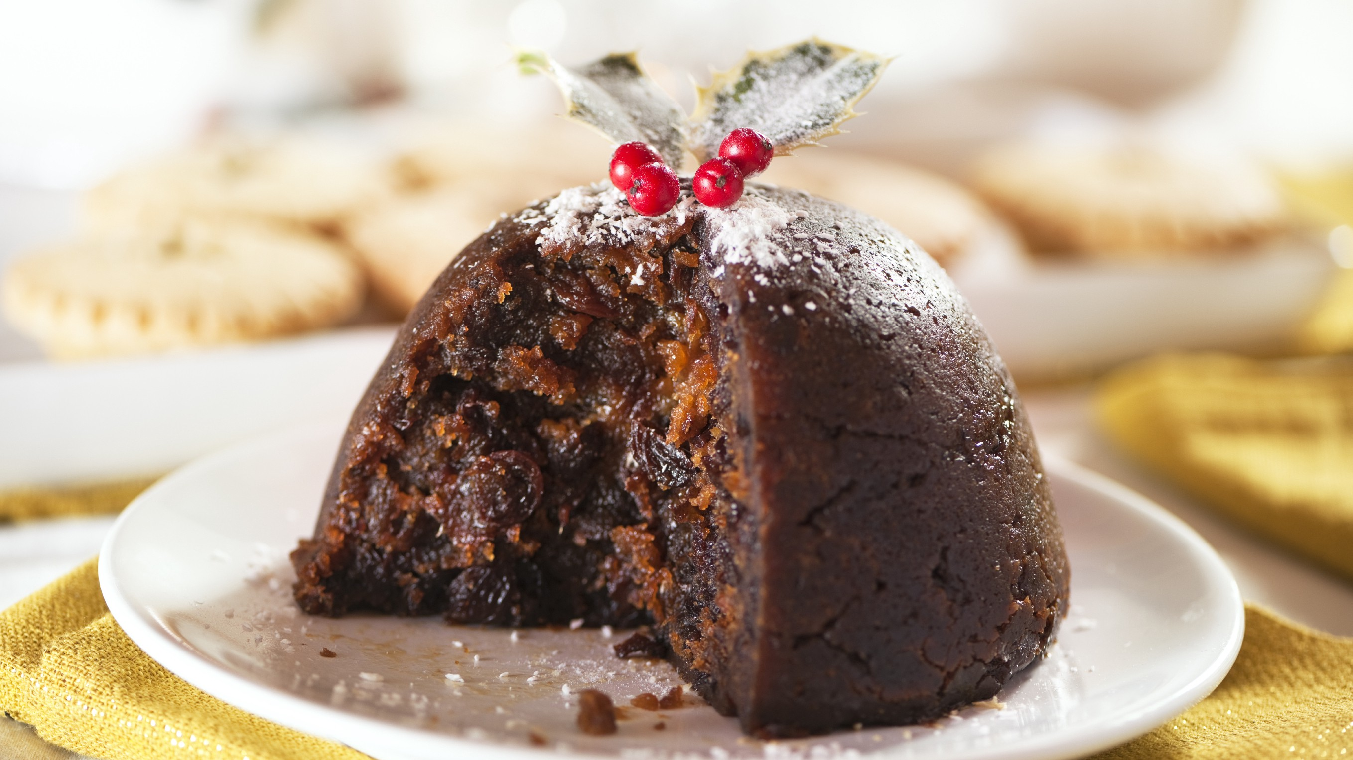 a fig pudding on a white plate, topped with powdered sugar and holly